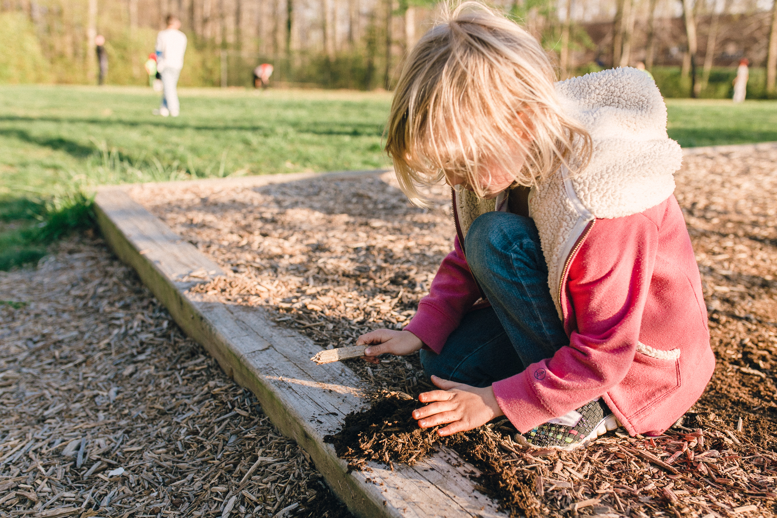 girl plays in the mulch on a playground in edgewater md | candid photography Annapolis MD