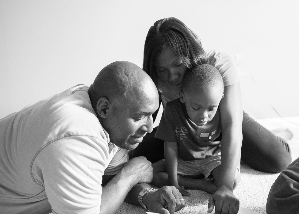 An Annapolis family reads books with their little boy during and in home maternity session.