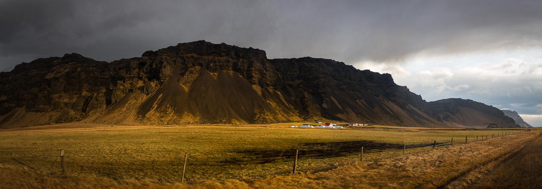 White Farmhouse and Mountain Range in Iceland