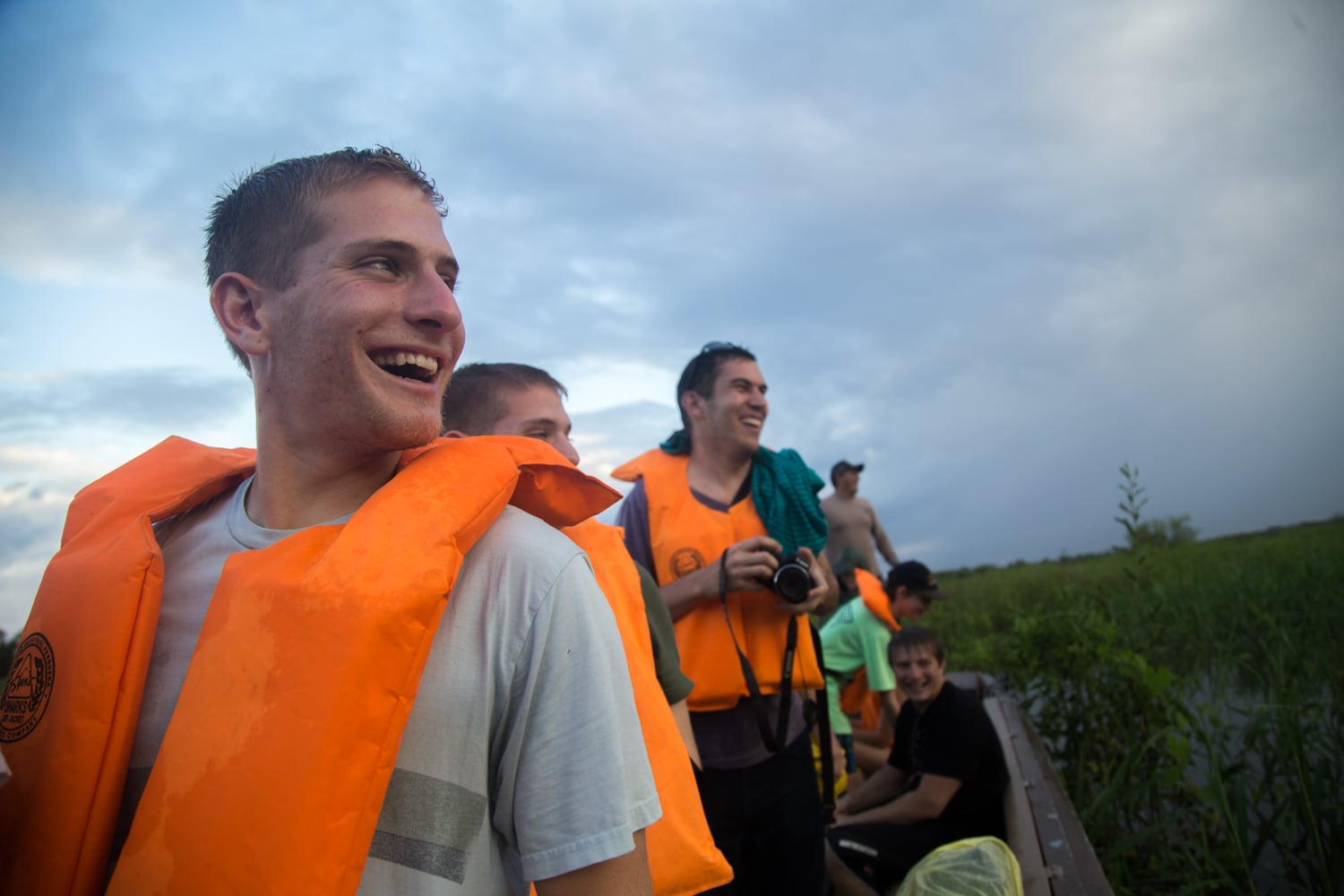 Jesse Axelowitz, Ryan Axelowitz, Jason Stoll, Corey Axelowitz, Nico Frost, and Juan Carlos look over as the people on the second fishing boat catch piranhas in the Amazon River