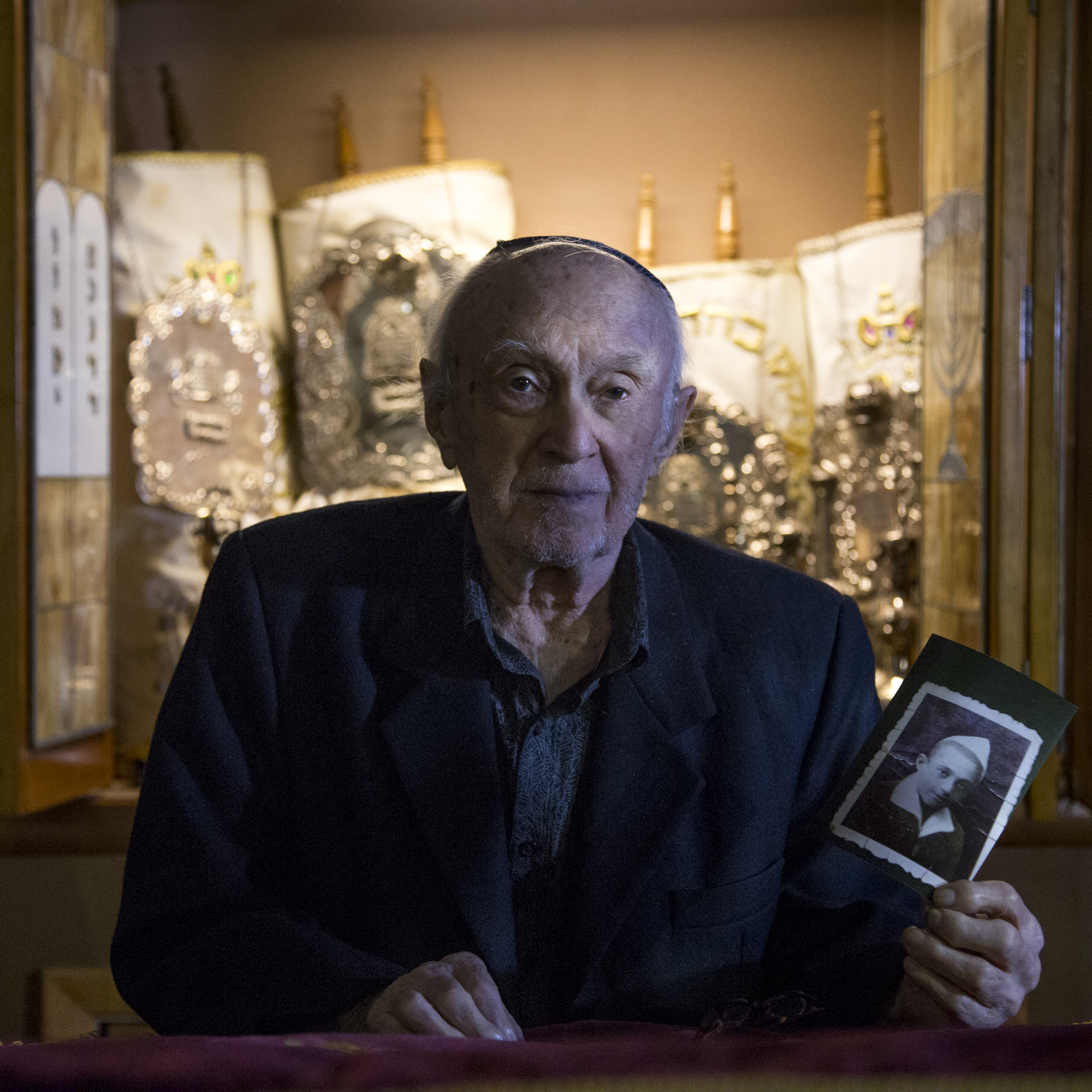 Holocaust survivor Chaim Ben-Aron holds a photo of himself just after liberation. He poses in front of the Torahs at his son's synagogue on Staten Island.