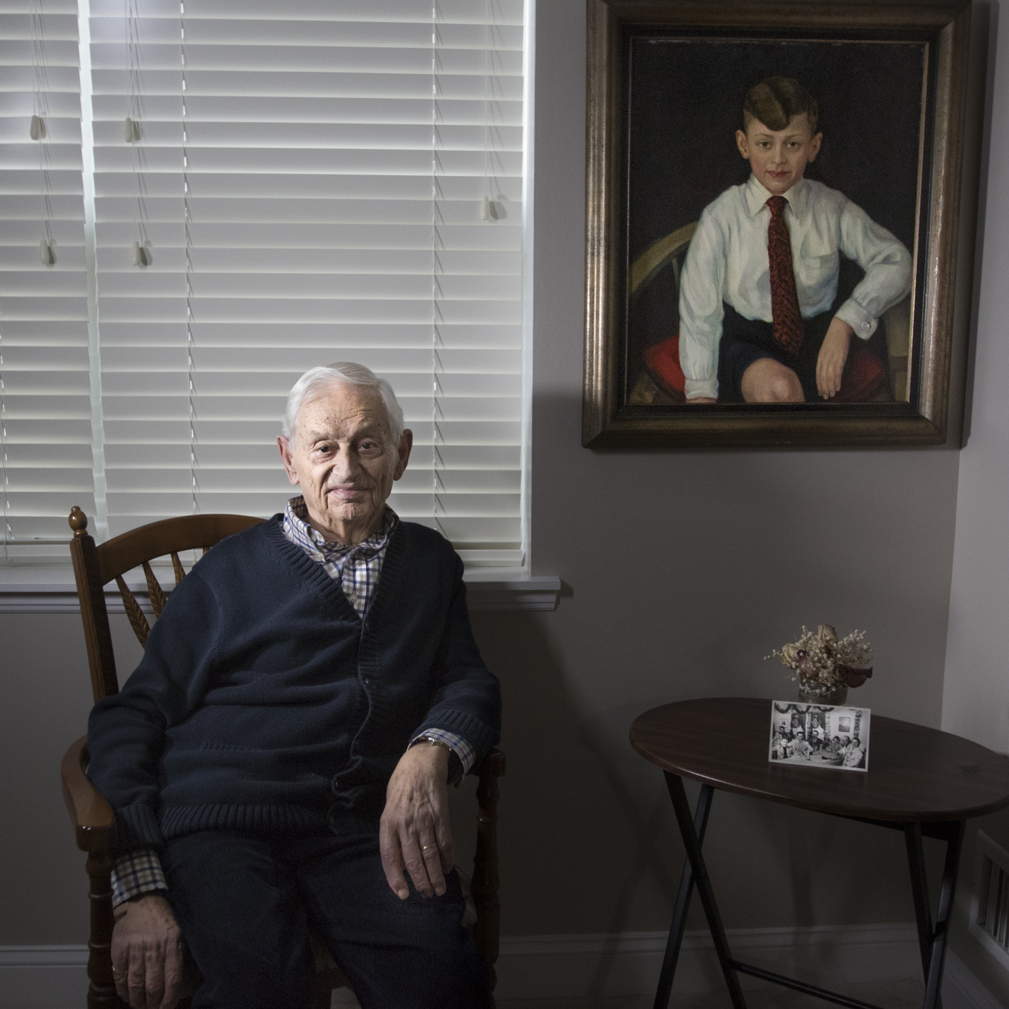 Egon Salmon poses next to a painting of him which was made in Rheydt, Germany in 1933, when Salmon was 9 years old. The portrait traveled with him on the S.S. St. Louis, to Belgium, and eventually to the United States in 1940. The small photo leaning against the flowers pictures him with his mother, sister, and other passangers at his table on the St. Louis ship. Shortly after his arrival to the United States, he settled with his family on Staten Island and was drafted to fight overseas in the American Army.