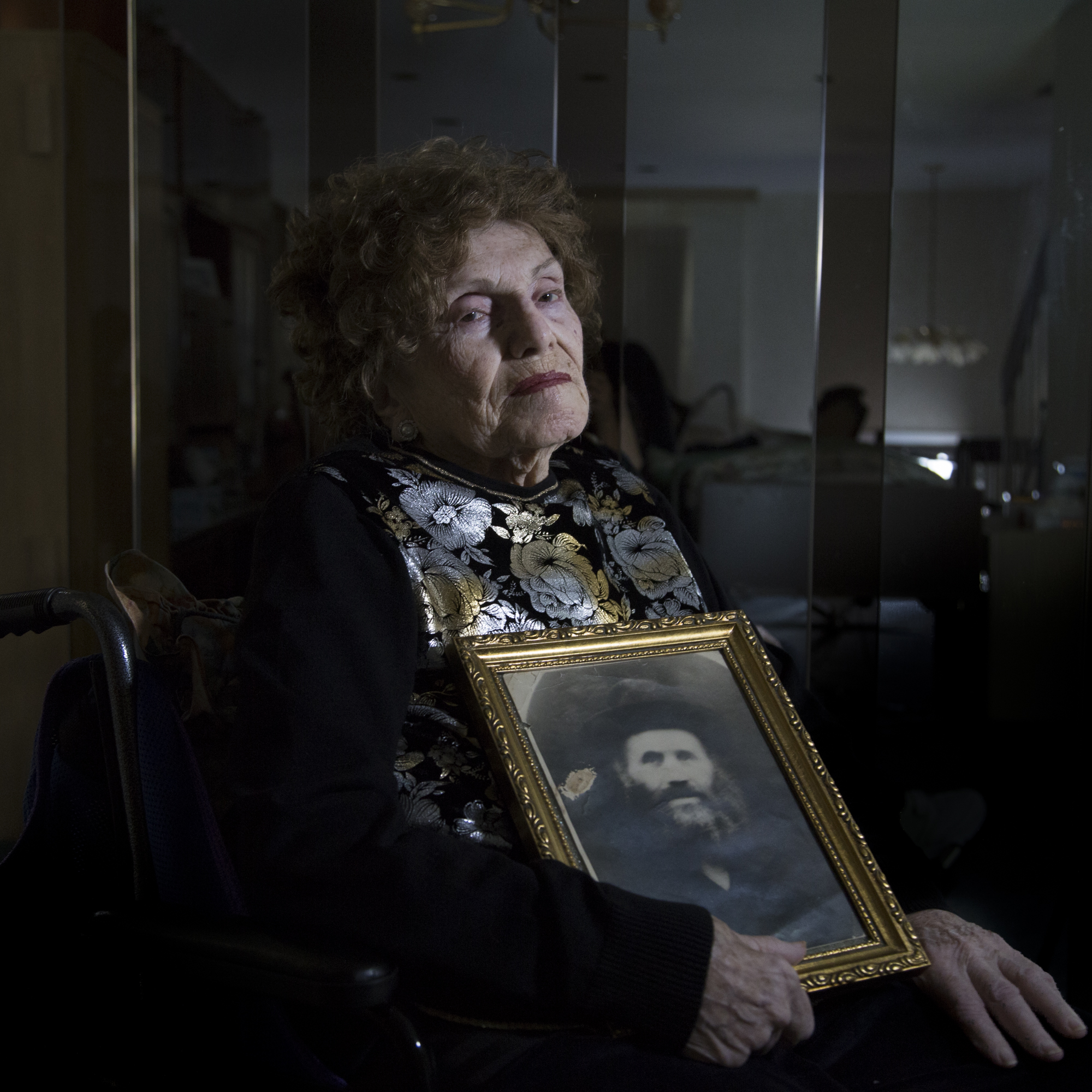 Portrait of Auschwitz survivor Rachel Gottlieb holding a photo of her father. The last time she saw him, she handed him his tallis (prayer shawl) and tefilin (a prayer leather box containing verses of the Torah inscribed on parchment) in the Dragomiresti ghetto. Shortly after, he was killed in the crematorium at the Auschwitz concentration camp.