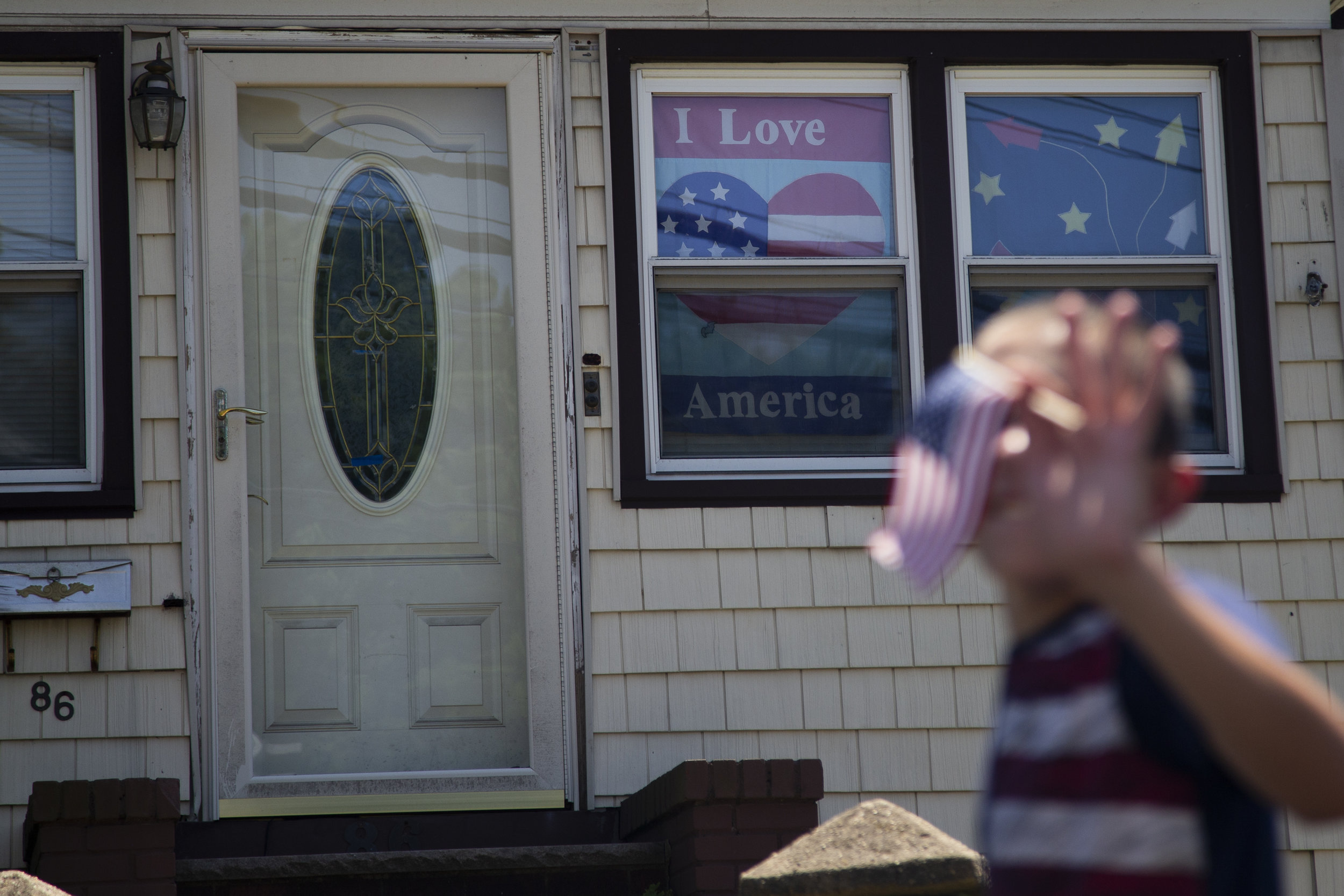 A young boy waves an American flag during the Travis Fourth of July Parade in Staten Island on July 4, 2019.