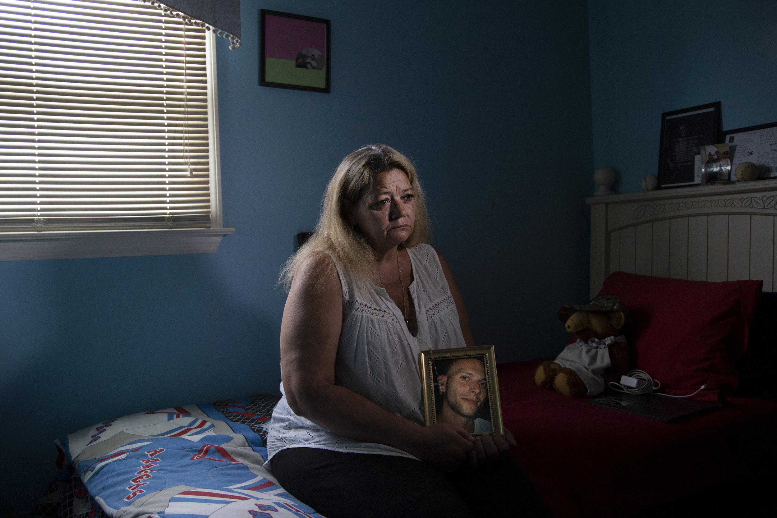 Sandra King sits in a guest bedroom that John would frequently stay in her home and holds a photo of her son, John King, who took his own life on October 7, 2017.