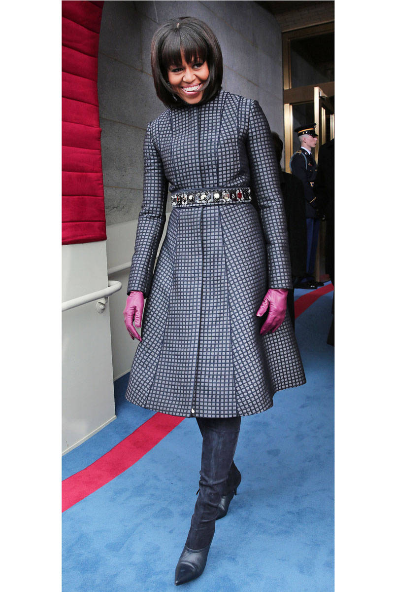 The stylish First Lady preparing to make her way through the Capitol during the Inauguration Parade in a navy and light blue checkered coat by Thom Browne, Reed Krakoff boots, and J.Crew accessories.