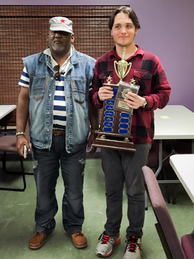 2016 Central Florida Chess Club Champion Kai Tabor (2034) (R) holding the club trophy after winning the event with a half point tiebreak lead over Alfonso Gabbedon (2161) (L) last weekend.