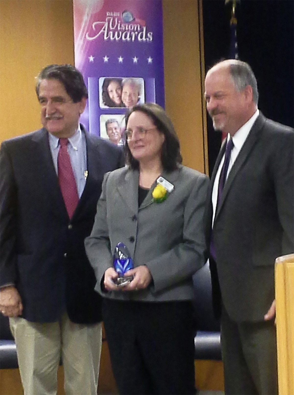 September, 2015Robin LeoGrande accepts the Texas Department of Aging and Disability Services Vision award in the category of Choices  From John J. Cueller (Left) Chairman of the Texas Aging and Disability Services Council, and Jon Weizenbaum Commissioner for the Texas Department of Aging and Disability Services (DADS)