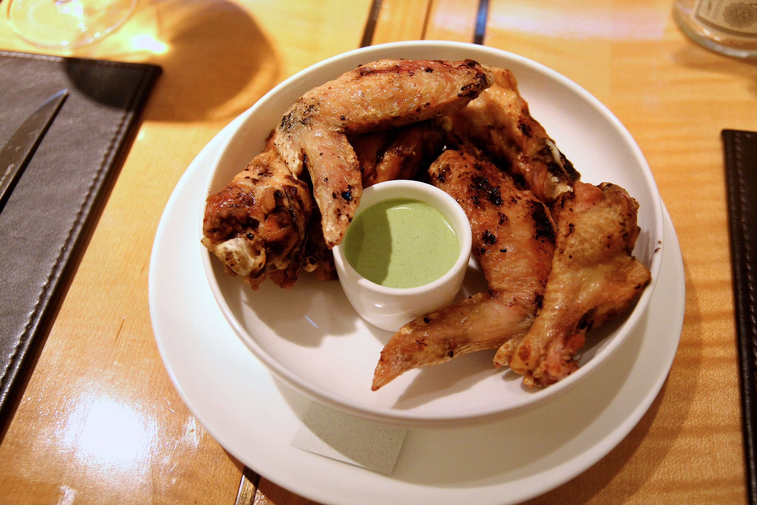 "Grilled Mary's chicken wings in a basil seed vinaigrette and a house made ""green goddess"" dip"