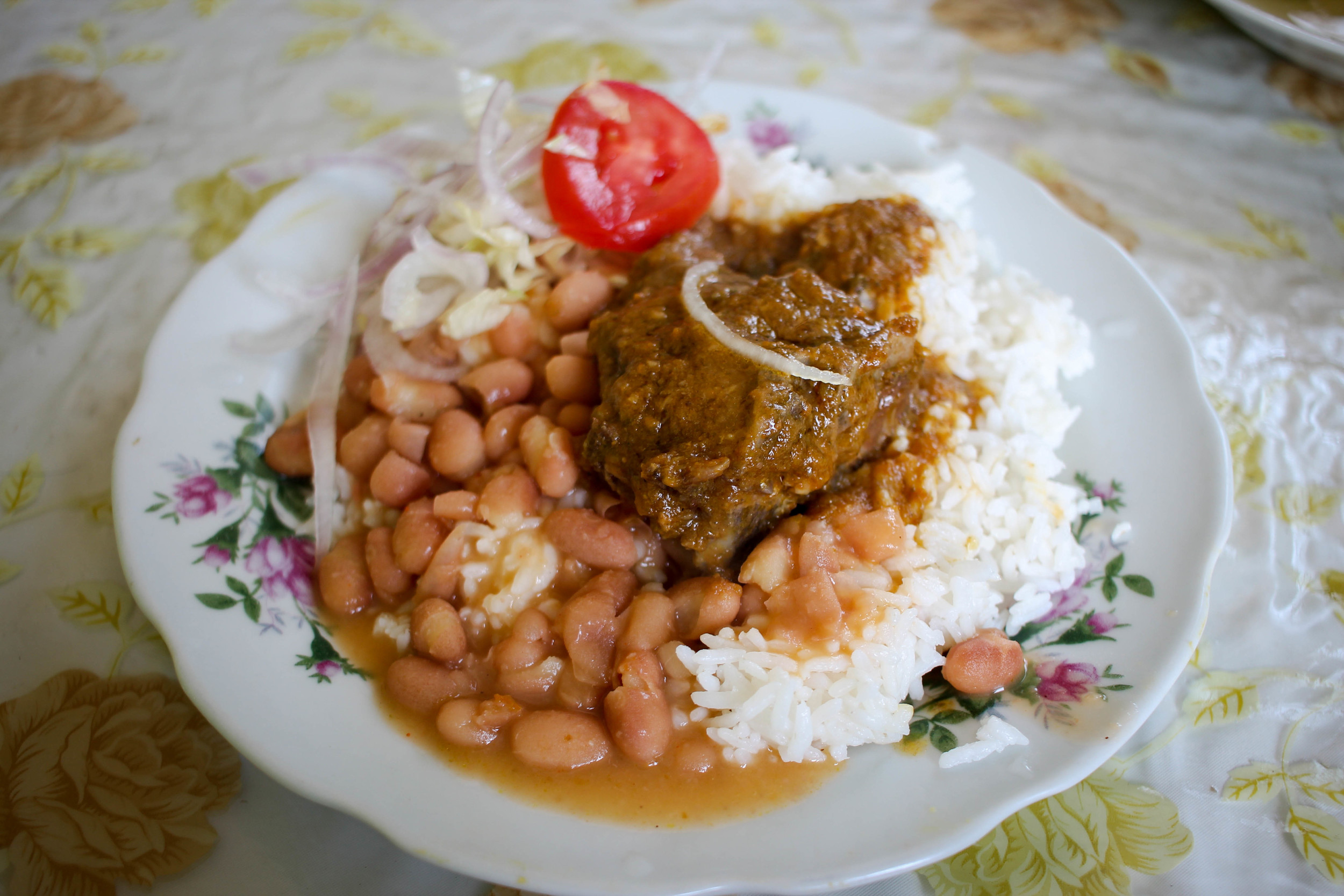 Stewed meat with menestras (beans), rice, and salad (i.e. red onion, iceberg lettuce, and a slice of tomato).
