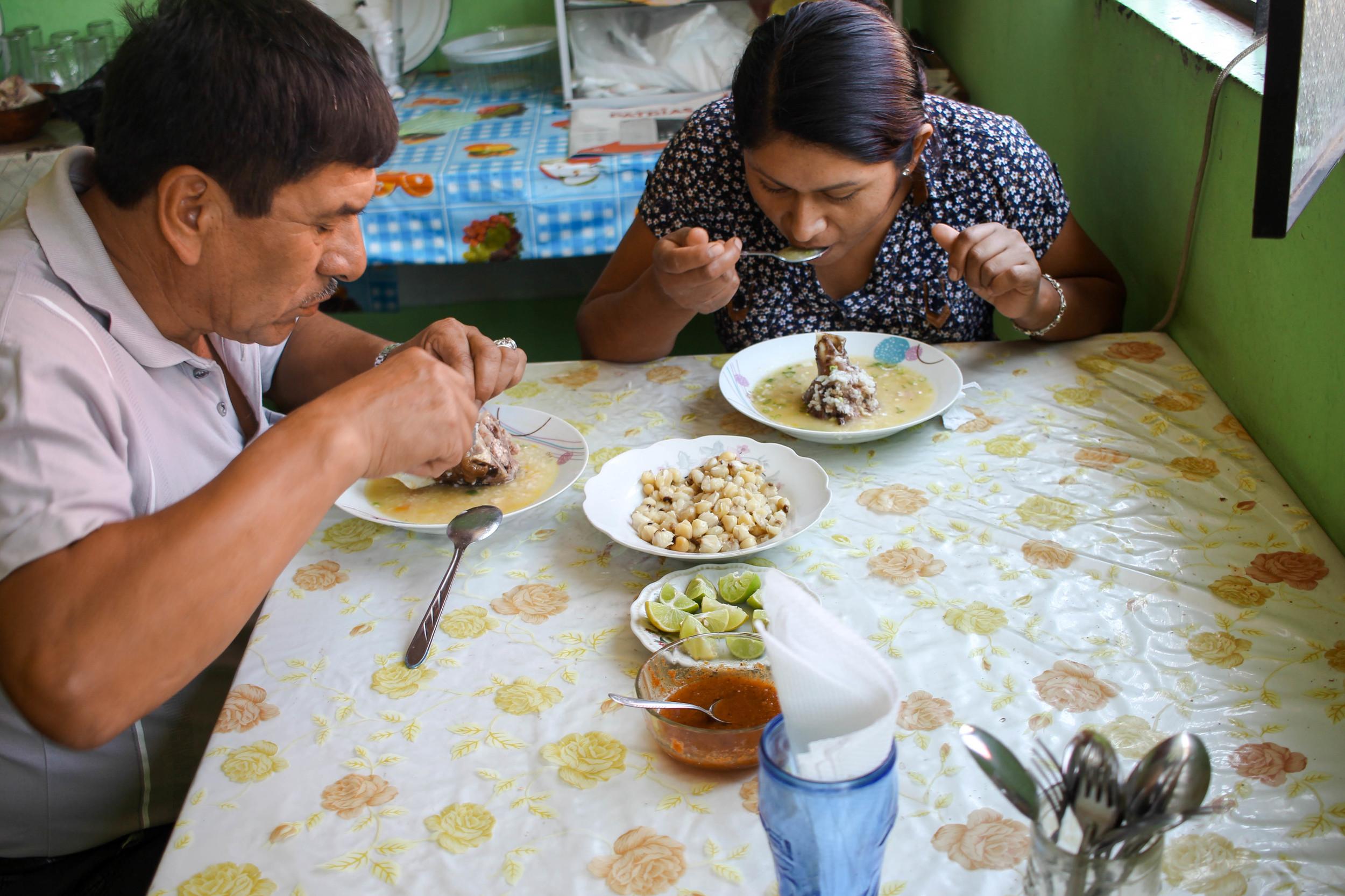 Hungry patrons eating caldo de cabeza.