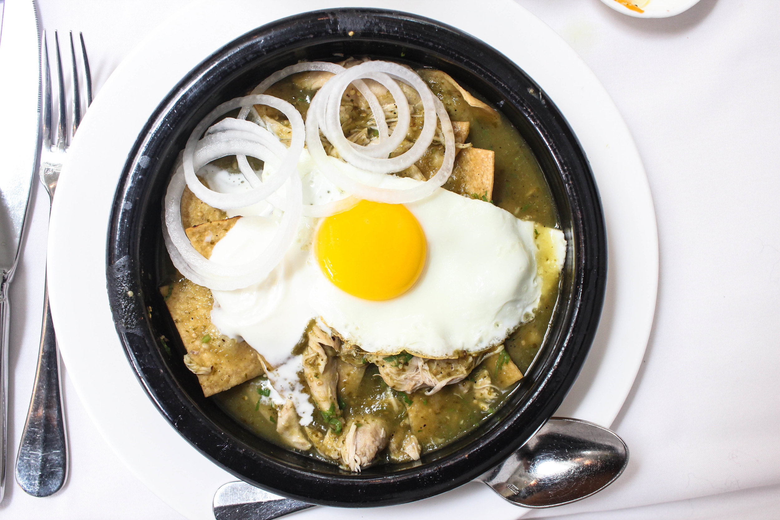 Chilaquiles verdes with chicken and a fried egg -view from above