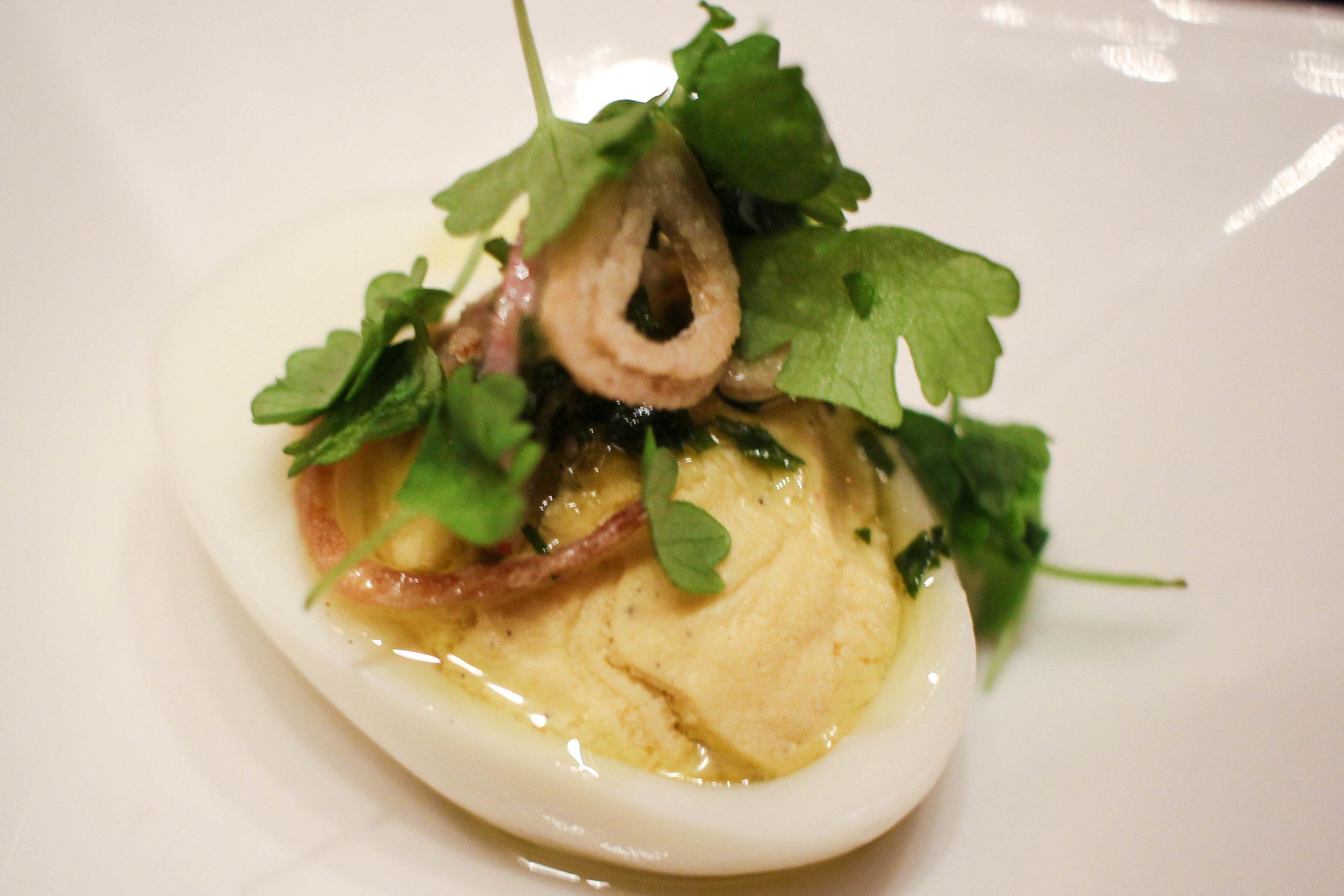 Deviled egg with salsa verde, breakfast radish, crispy shallot
