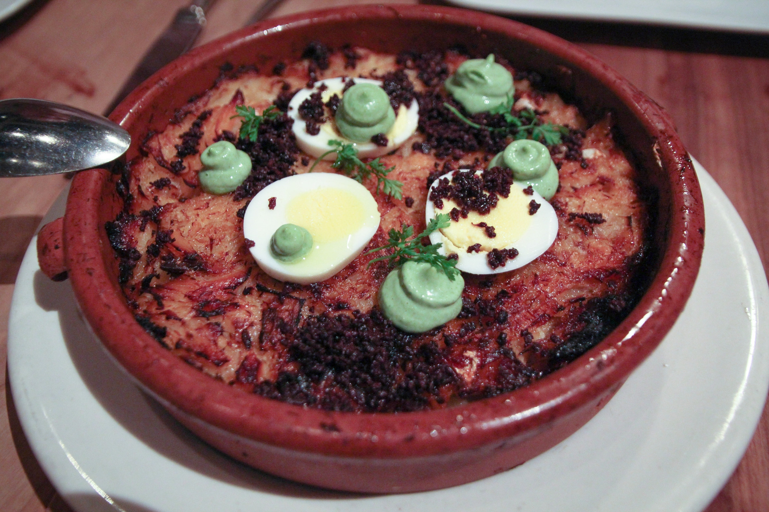Bacalhau Gomes de Sá: baked salt cod casserole, potatoes, caramelized onions, parsley aioli, crumbled olive, egg