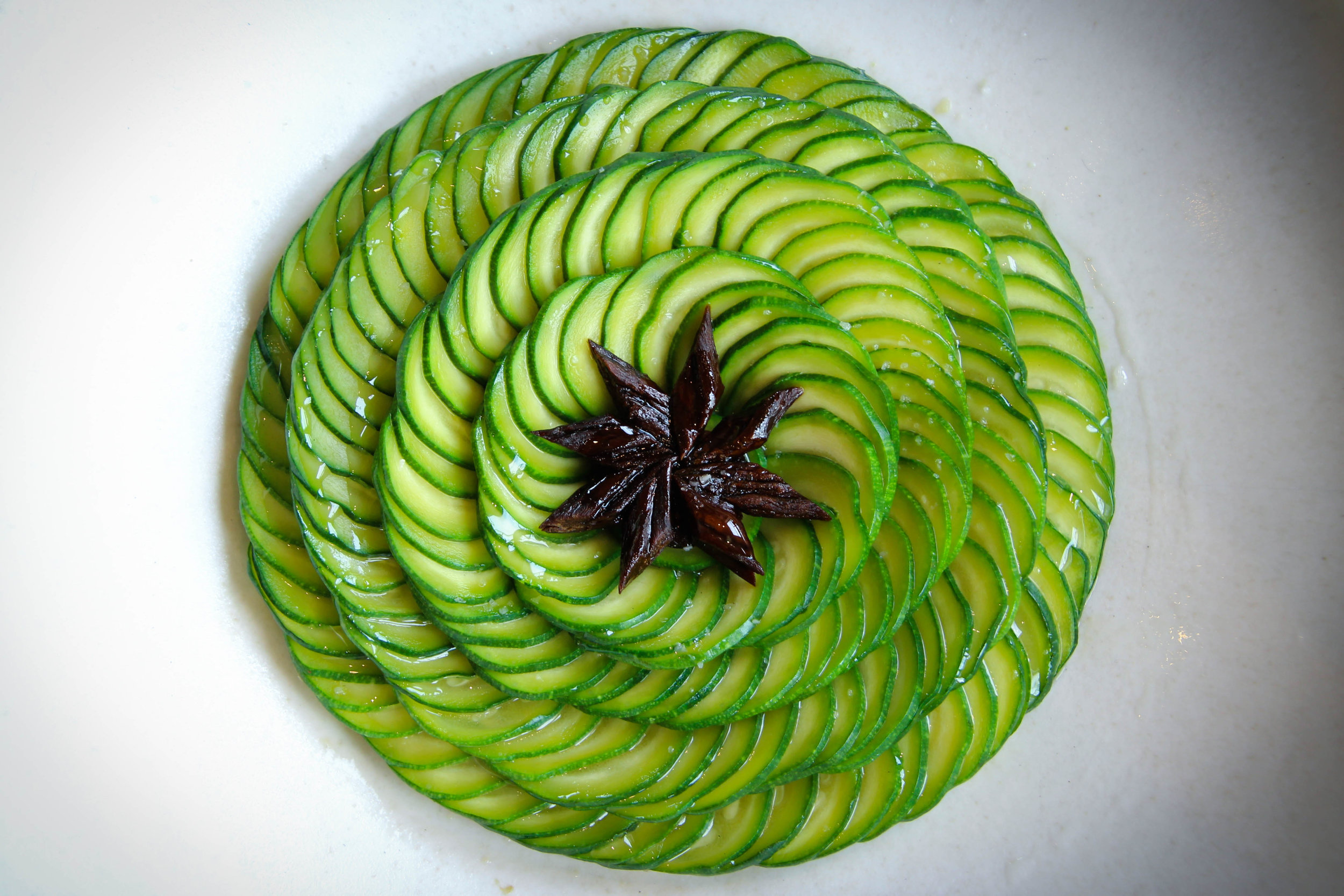 Slices of green courgettes with salted plums and roasted yeast oil.