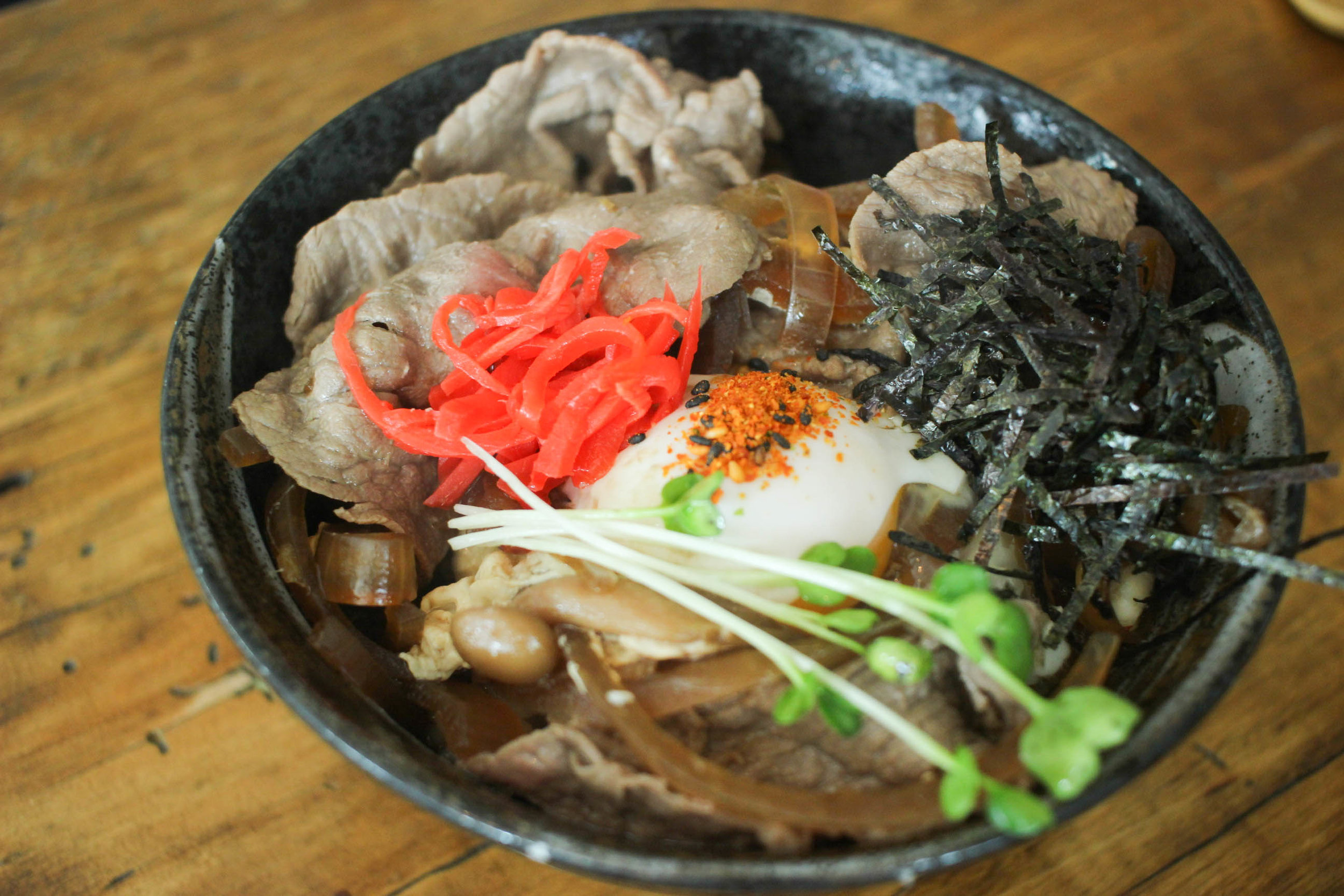 Gyodon: thinly sliced kobe beef, cooked in sweet ginger soy sauce with onions, served over rice with a poached egg.