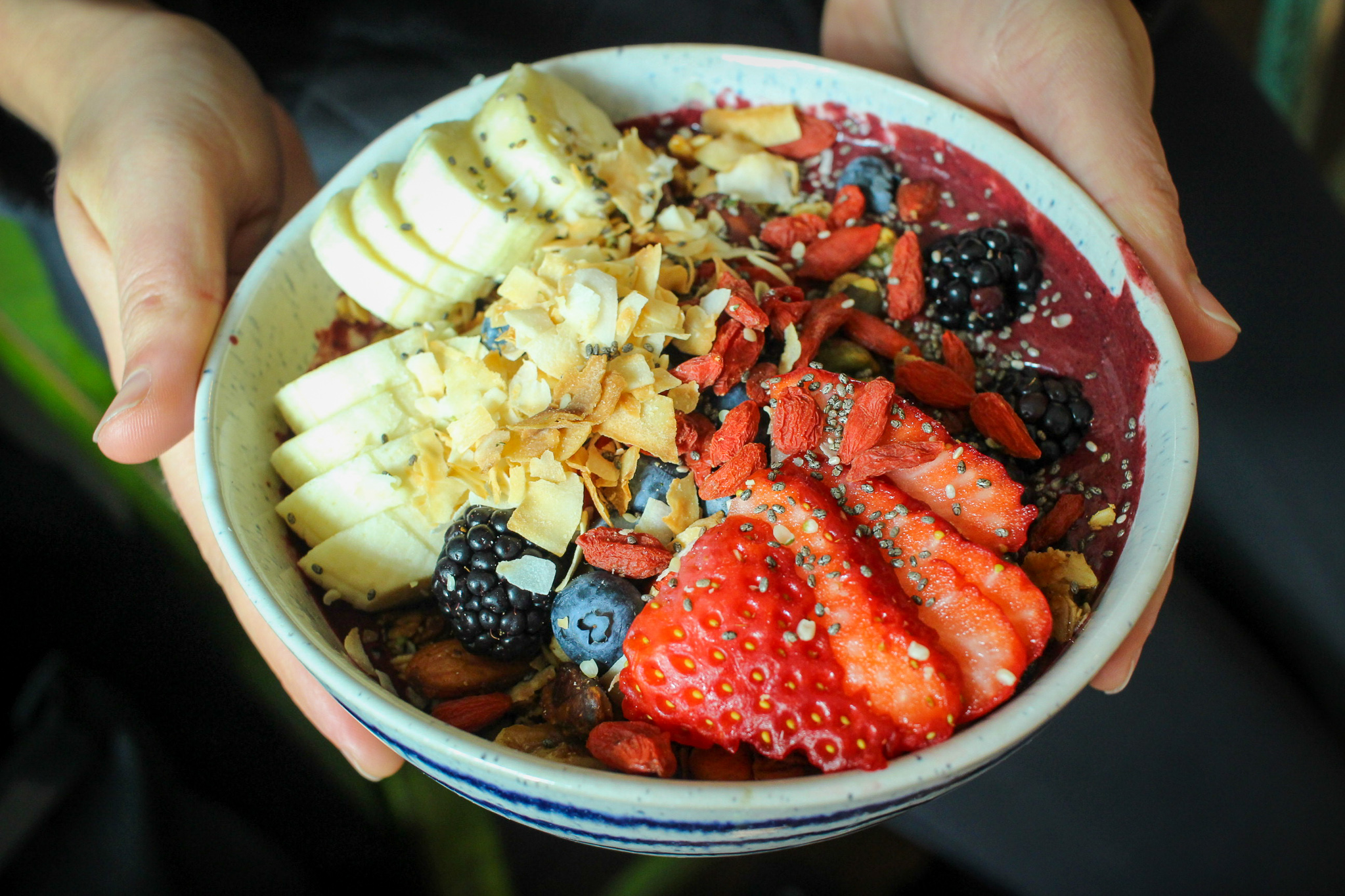 Red velvet smoothie bowl: beet, avocado, berries, date, cocoa, coconut butter, nut milk, and maca–topped with homemade granola, banana, goji berries, cocoa nibs, coconut and hemp seeds.