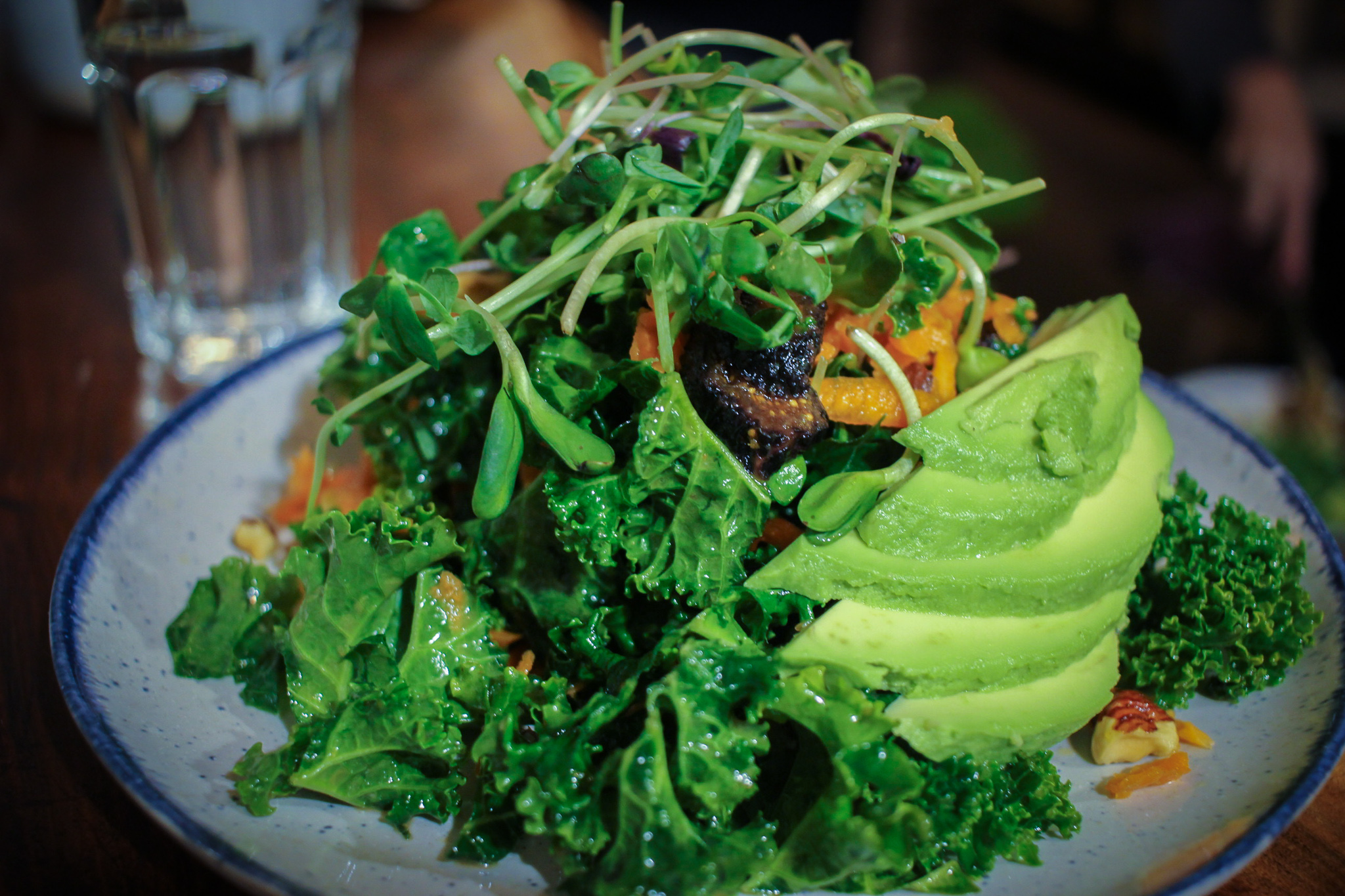 Citrus, hazelnut, and kale salad: kale, carrots, sprouts, orange slices, toasted hazelnuts, dried figs, avocado, and an apple cider vinaigrette.