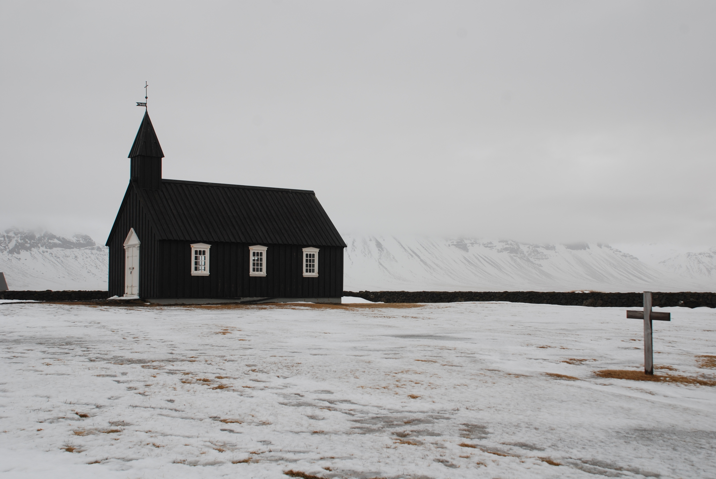 """This church sits outside of Hotel Budir, situated in a lava field on the westernmost tip of the Snaefellsnes peninsula. The day spent on the peninsula was an interesting one—driving hours without seeing a soul, the vastness of the landscape hard to comprehend.The sun just went down, it was freezing cold, and there were just a few cars left on the newly dark road. In an attempt to capture a photo of the sunset, we veered off the rode unknowingly into a snow covered ditch.Car after car pulled to the side of the road, but there wasn't much that could be done. A woman with her kids in the car offered to help """"push,"""" but the task was greater than her kindness.Finally, after about an hour of trying to dig the car out, an older Icelandic gentleman in an old Land Rover Defender pulled to the wrong side of the road. He took rope from the back of his pickup and tied his truck to ours without speaking a word—we couldn't speak his language, he couldn't speak ours. He put his truck in reverse and took us with him. Sometimes just a look, an act of kindness, a refusal of payment, a hug, and a smile transcend."""