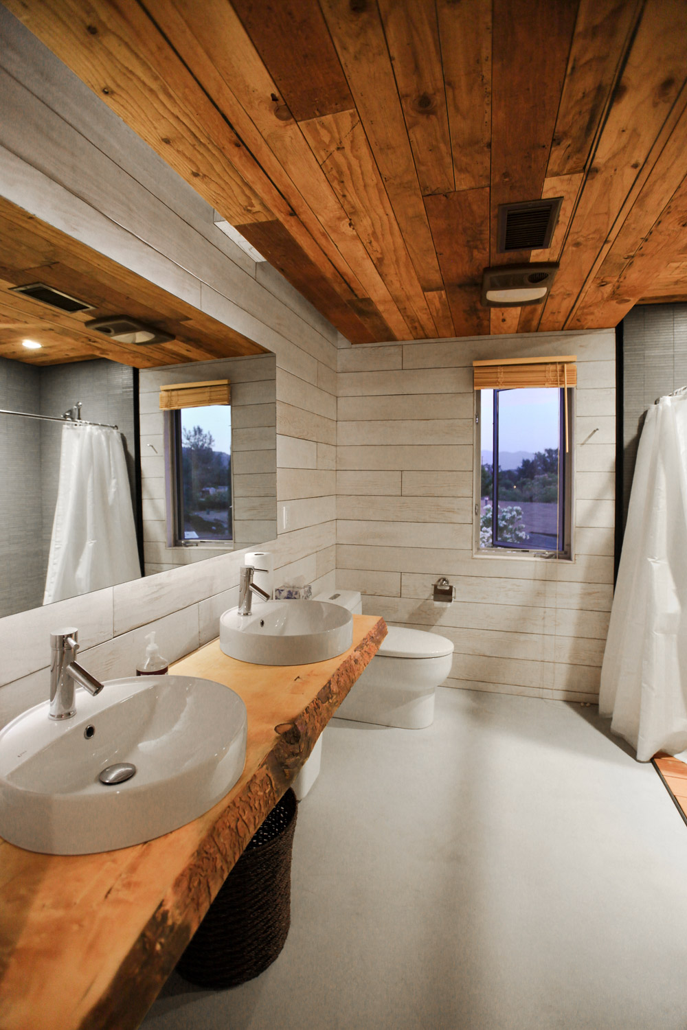 510 Cabin modern bathroom combines whitewash plywood with a reclaimed wood slab vanity sourced from a forest fire in Lake Arrowhead California. The ceilings are made from reclaimed structural plywood deconstructed from a demolished house in Los Angeles.