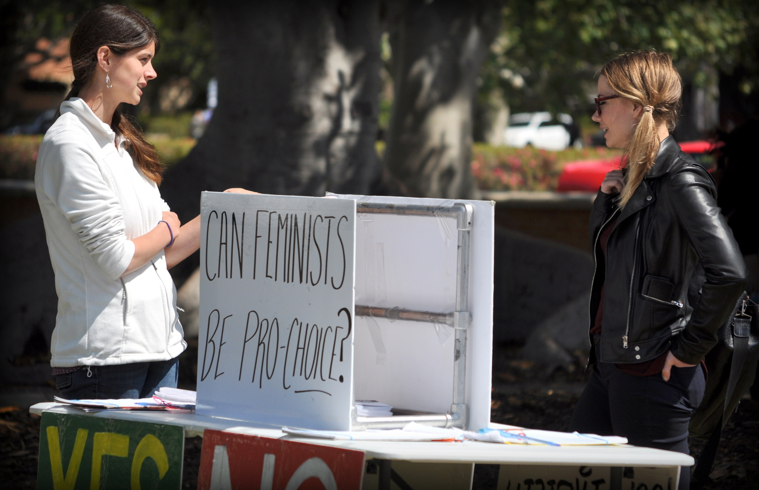 "JFA Trainer  Rebecca Haschke  talks to a UCLA student (May 2016) in front of one JFA poll table asking: ""Can feminists be pro-choice?"" The poll question's unexpected phrasing prompts many conversations about human equality and the pro-life position."