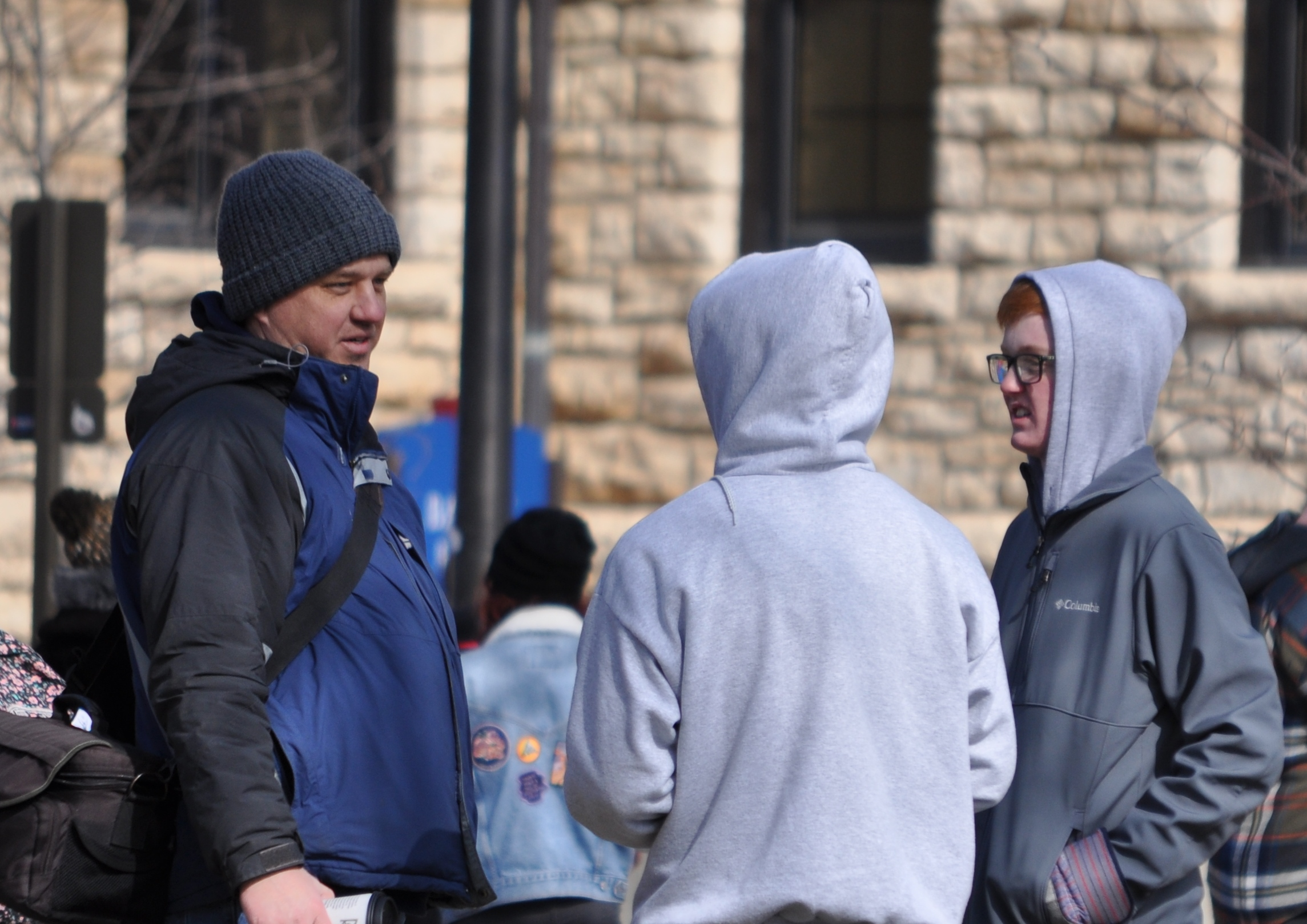 Sean (right) and Benjamin (center) talk to their JFA mentor, Paul Kulas (left), about Benjamin's first conversation at the KU outreach in March.