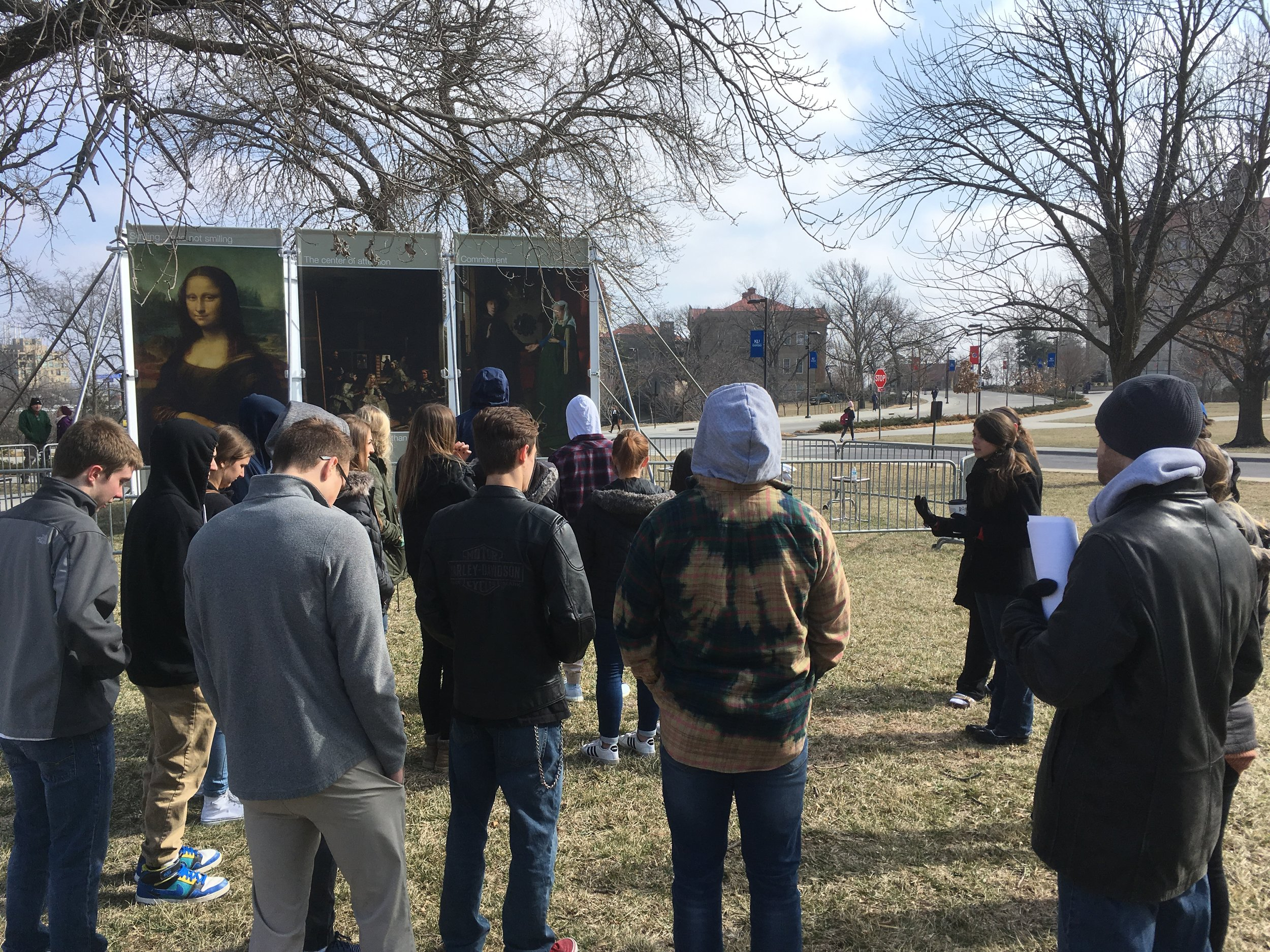 Spencer (right) and his students listen as Rebecca Hotovy describes JFA's   Art of Life   Exhibit at the recent University of Kansas outreach event in March 2018.