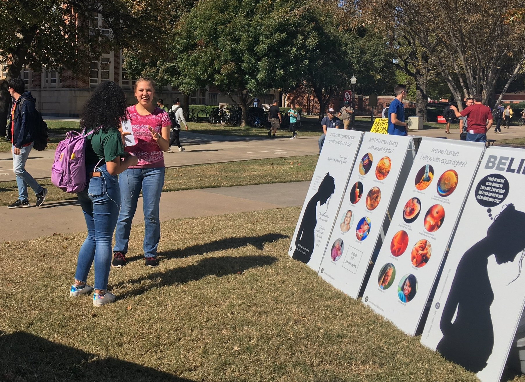 Kaitlyn Donihue (pink) creates conversation at OU. Note how the juxtaposed imagery of mother and child makes it clearer that we care about both.
