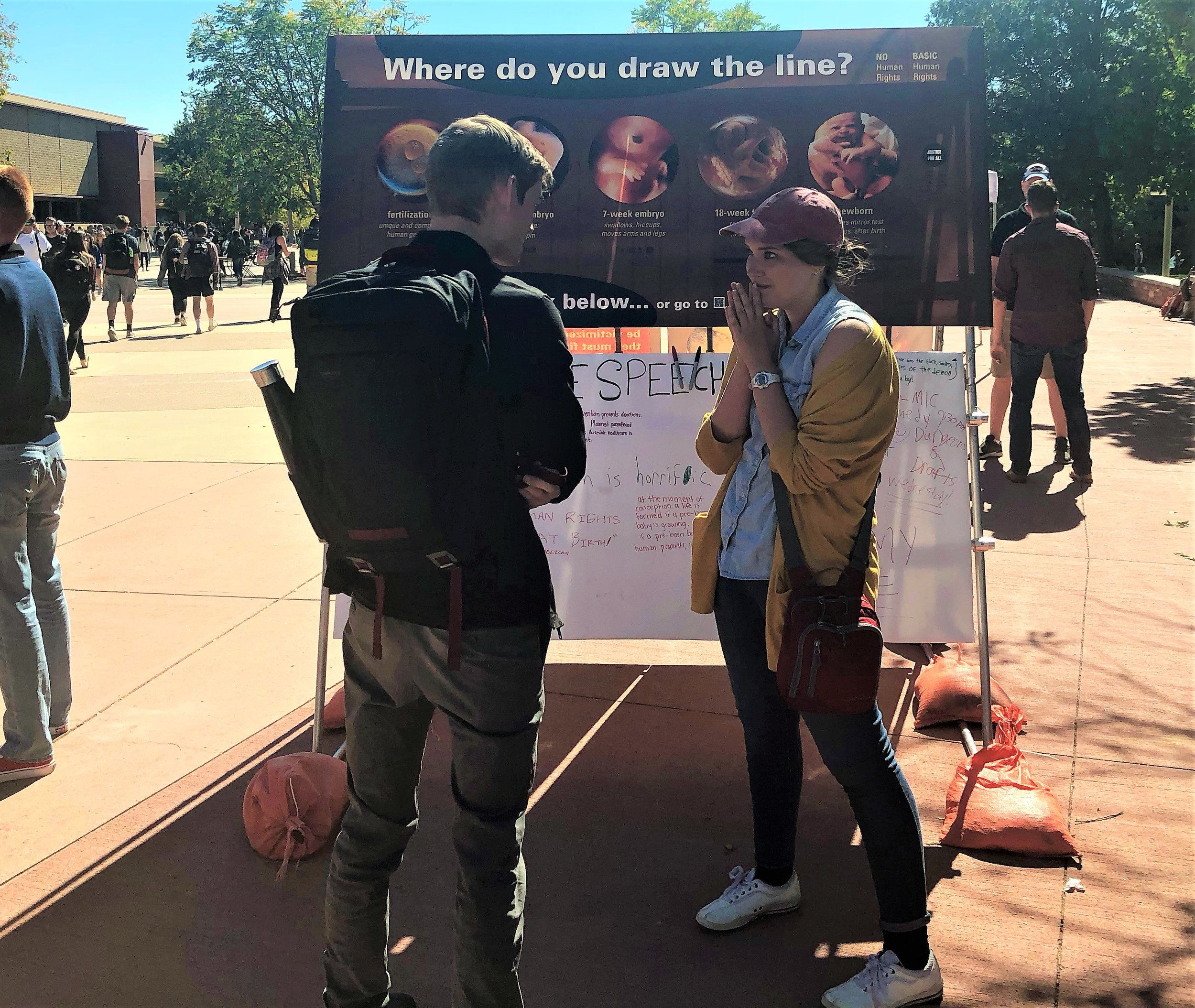 Above, Grace is shown talking through the question of whether or not the unborn is a human being with rights with a student at Colorado State University.