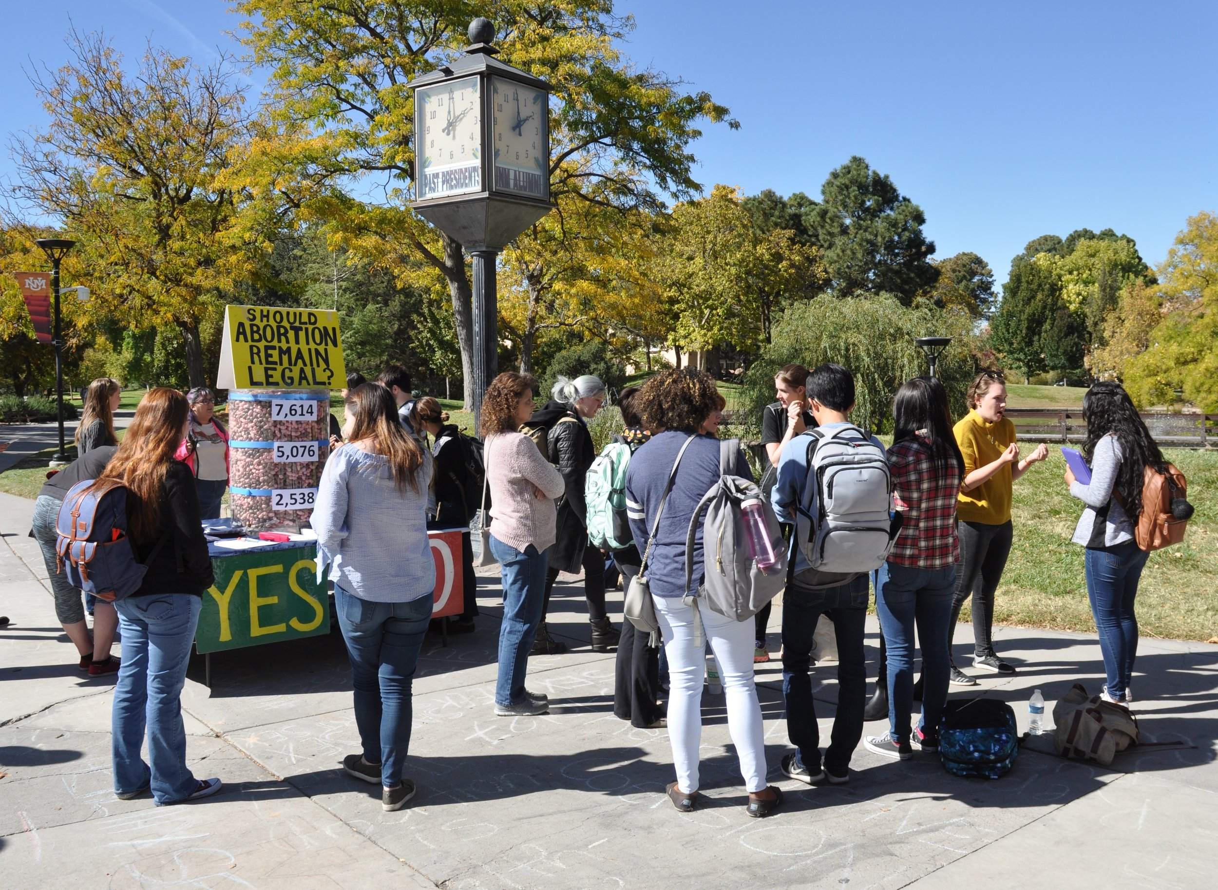Julia (far left, with backpack) observes conversations at  a 2017 JFA outreach event at UNM  during her first semester on campus. The transparent barrel under the yellow sign contains fetal models representing the children killed by abortion in America during the days JFA was on campus.