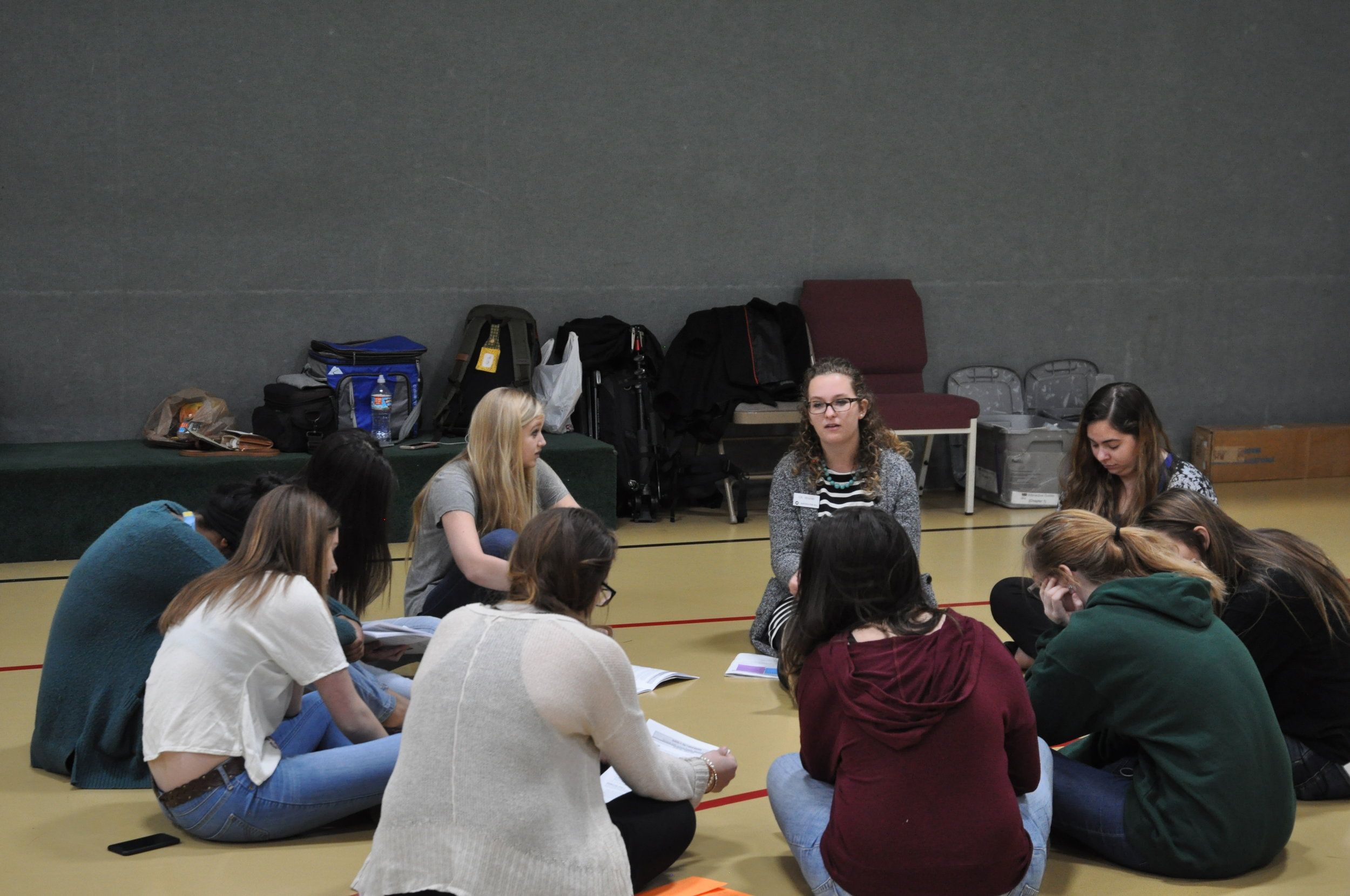Rylei's first exposure to Justice For All was during our seminar at her high school in 2017. Here JFA trainer CK Wisner (center, curly hair) leads her mentor group in interactive exercises and discussion as Rylei (facing CK) listens.