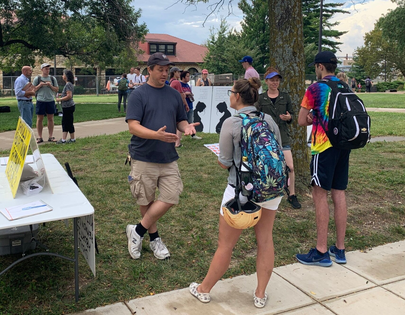 Thursday (KU):  Paul Kulas  (center) and volunteer Rebekah (second from right) interact with students near the poll table at KU.