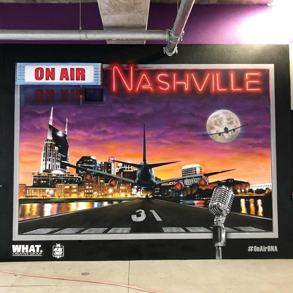 "On Air -  Nashville International Airport  On Air is a collaboration by Nashville based artists Jake Elliott and Eric ""Mobe"" bass. This piece was designed to give Nashvillians and visitors a fun interactive, and snap-shot worthy experience. The work's title is a play on words, paying homage to the rich musical history of Nashville and incorporating aviation and the aircraft that bring people to and from Music City every day."
