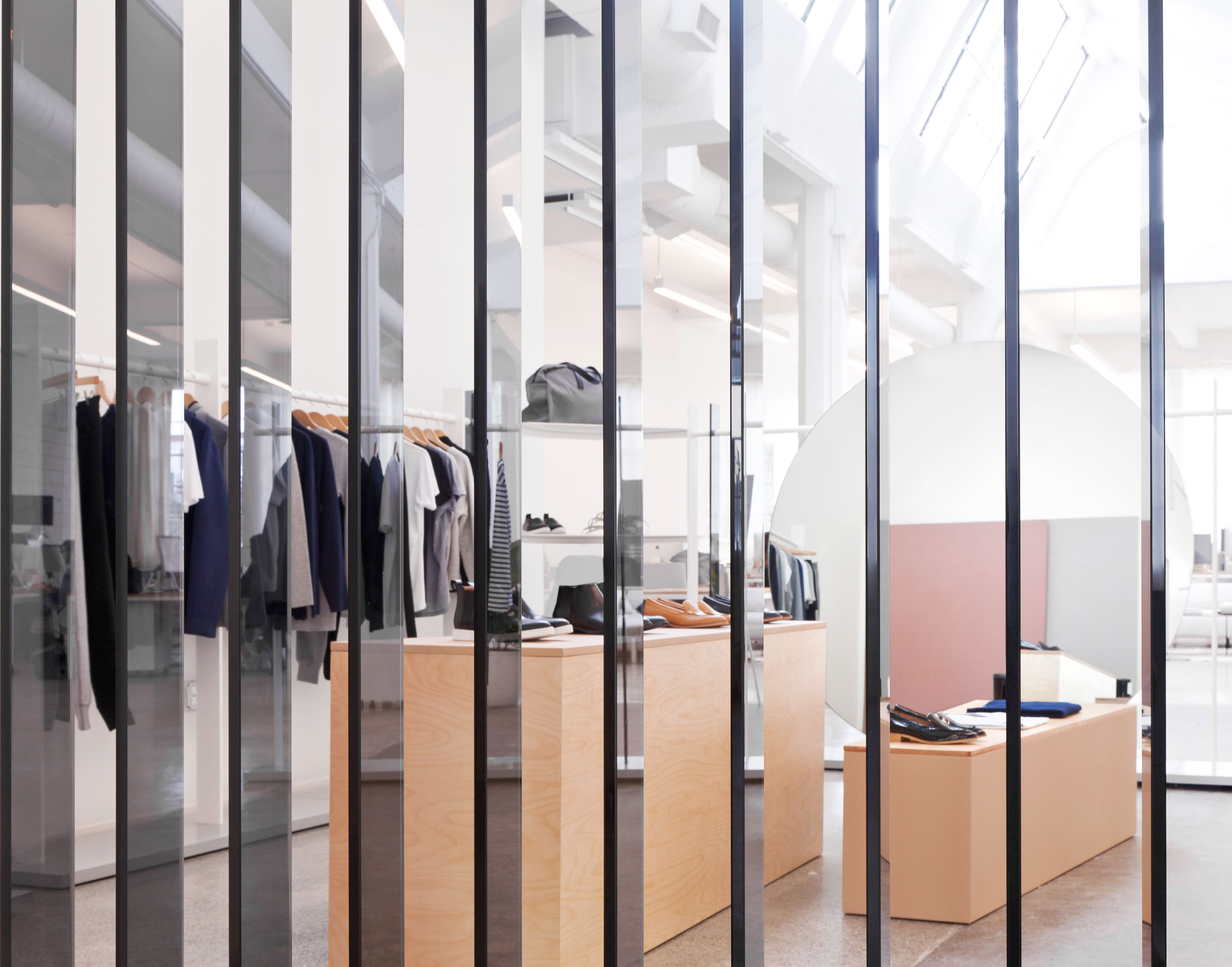 Smoked glass panels, suspended from a single steel tube, evoke Everlane's core values of radical transparency while creating a subtle division between their open office floor plan and the showroom's perimeter.