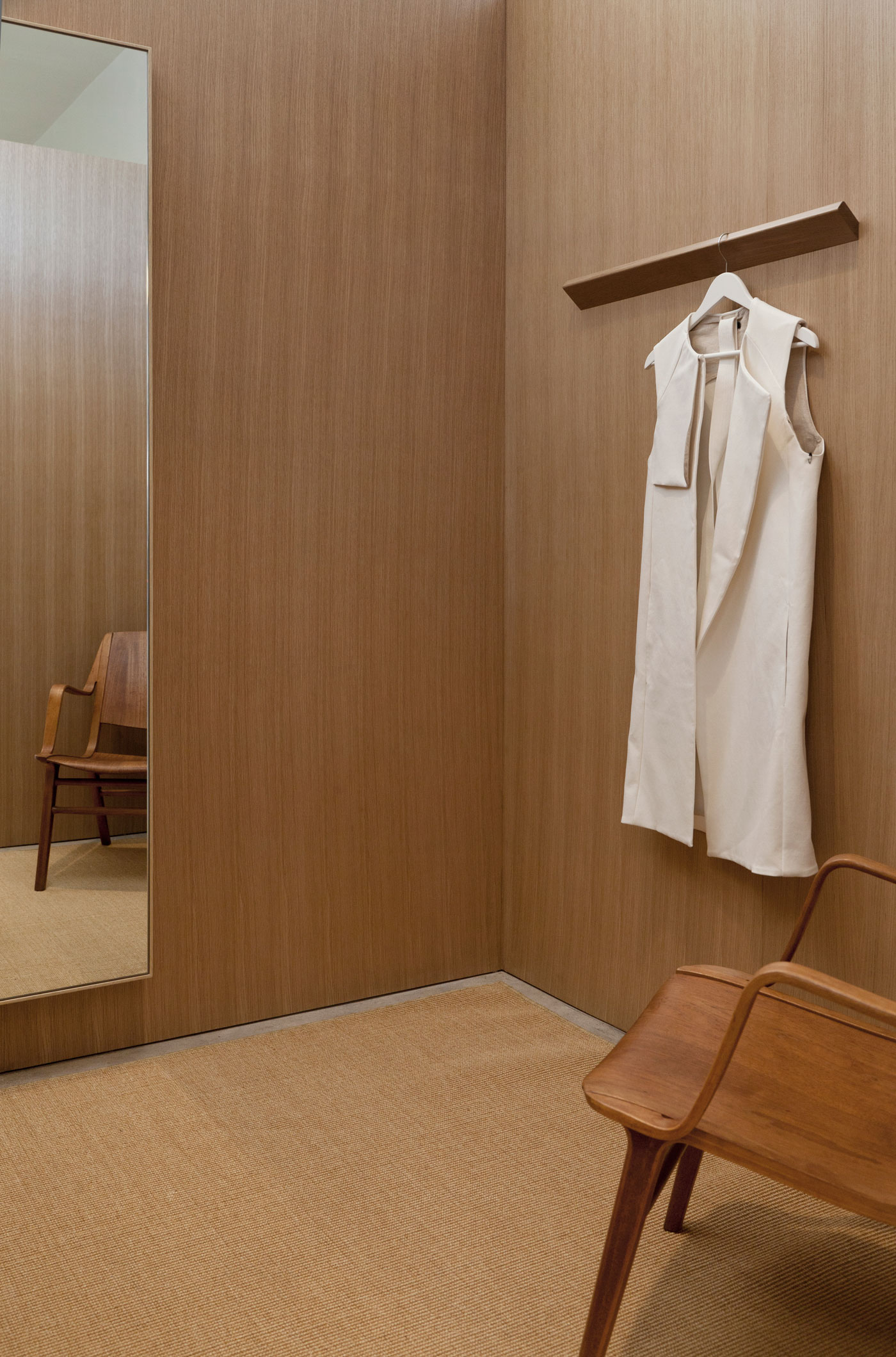 The oak clad fitting rooms feature custom designed hang rails sculpted from solid white oak. The subtle angle allows the rail to catch the clothing and light from above.