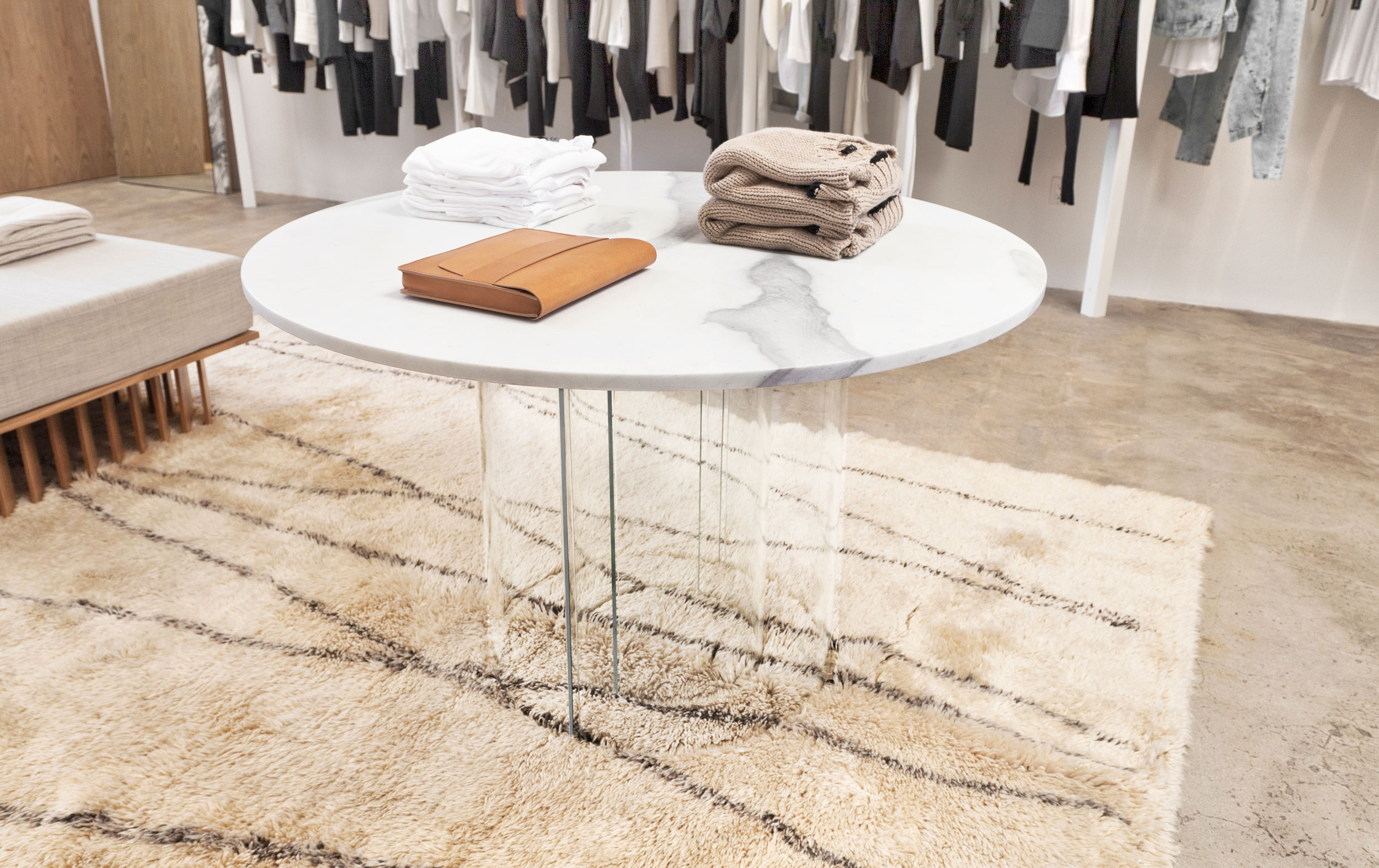 """Accessories and knits are presented above a round slab of milky white marble with washes of cool gray and distinct,""""ghost-like"""" markings. The natural stone appears to balance impossibly above four bent glass half-cylindrical bases."""