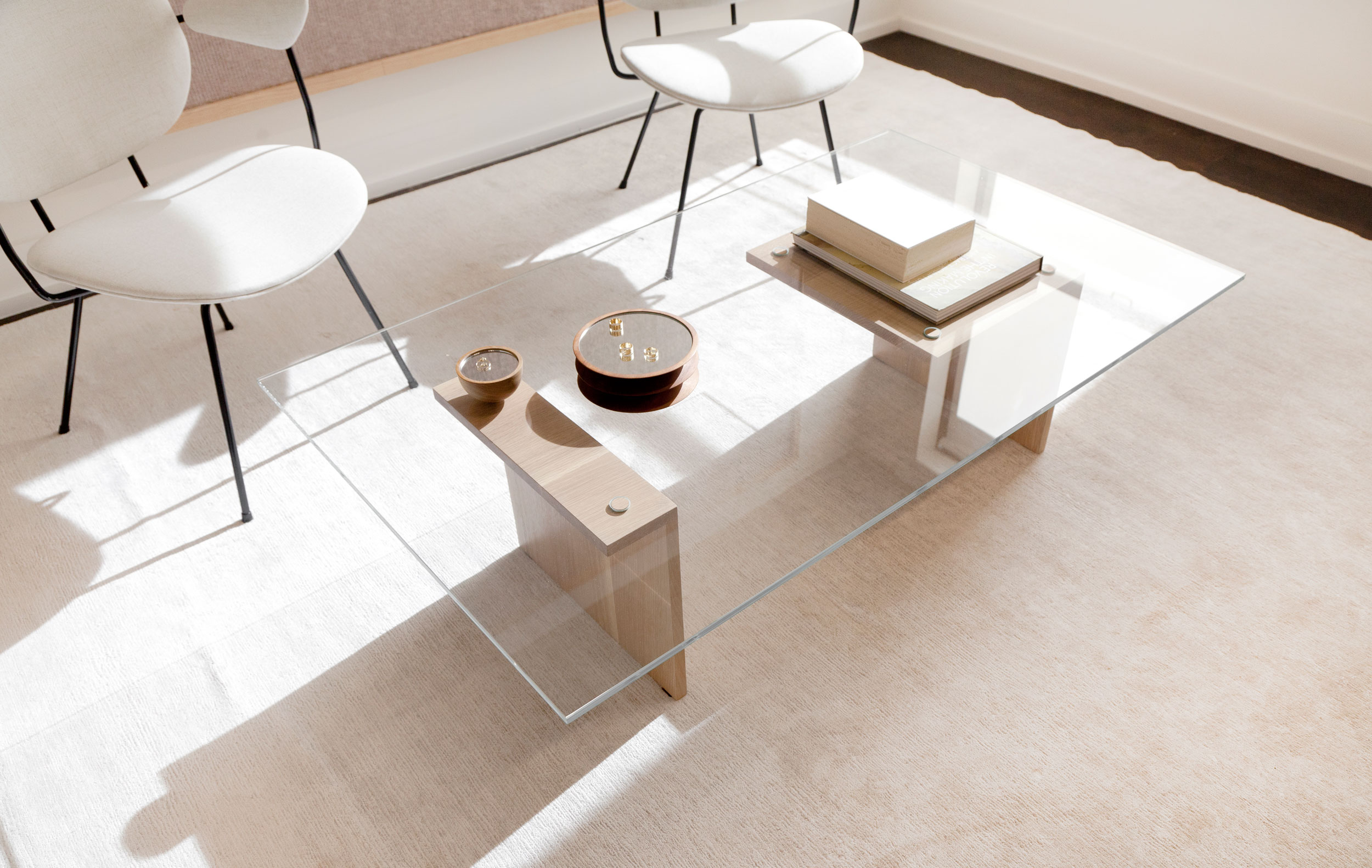 Custom, angular glass and white oak coffee table paired with rounded vintage chairs.