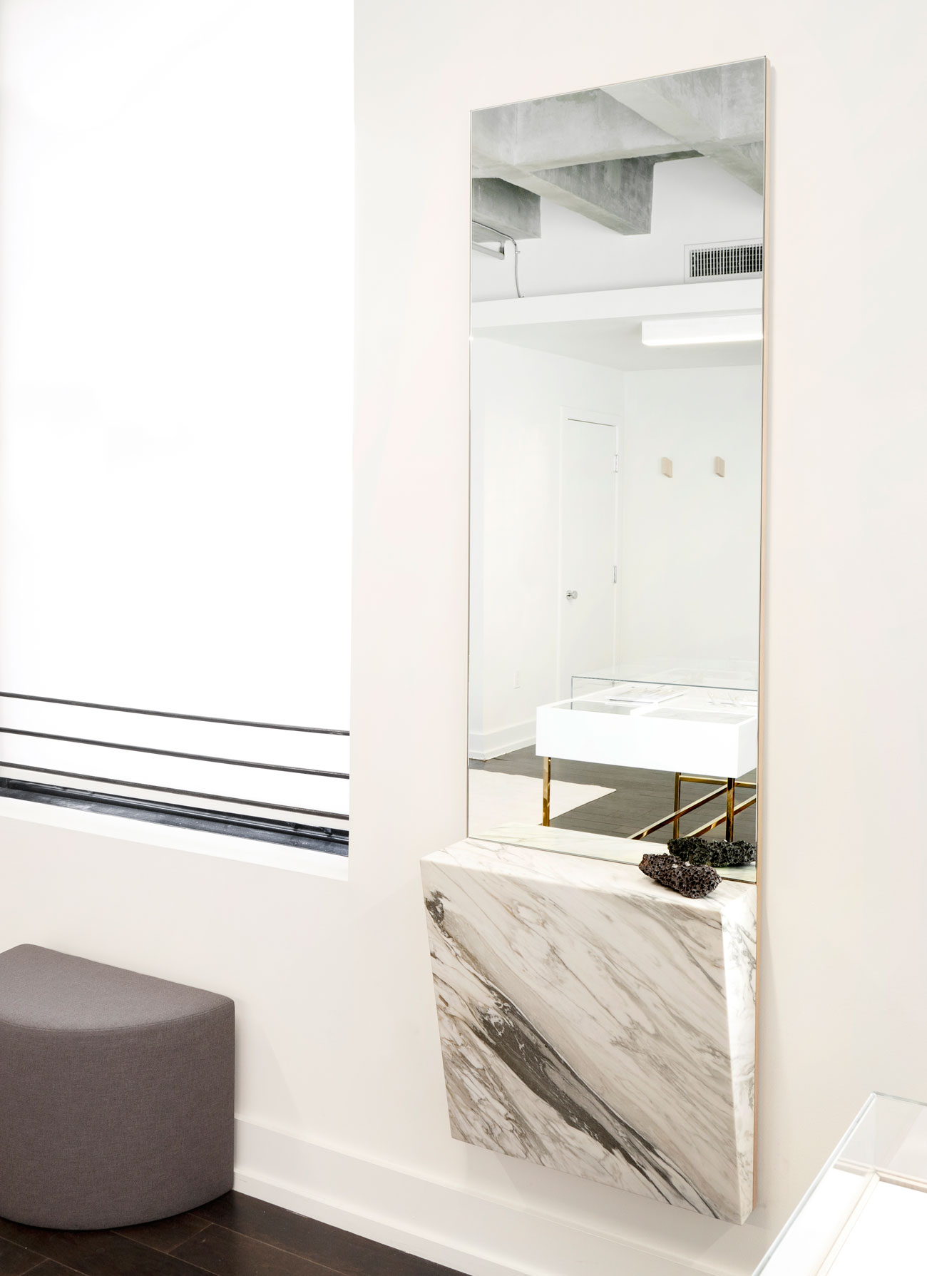 A wedge of Mountain Calcutta marble affixed to the wall-mounted mirror was designed to hold jewelry during fittings.