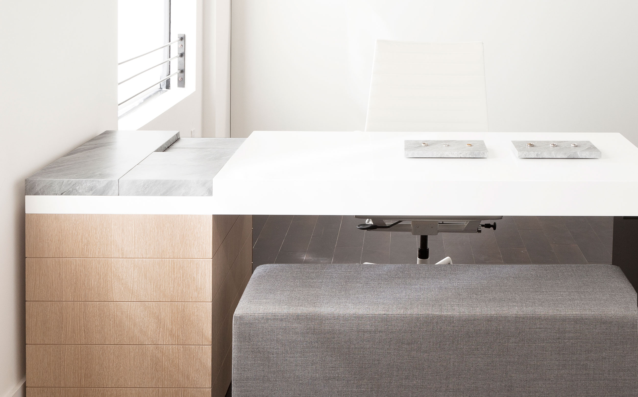 A single slab of marble was cut into smaller parts, and designed to fit into a recess in Grace's desk. During appointments, Grace is able use the felt-backed marble as presentation trays.