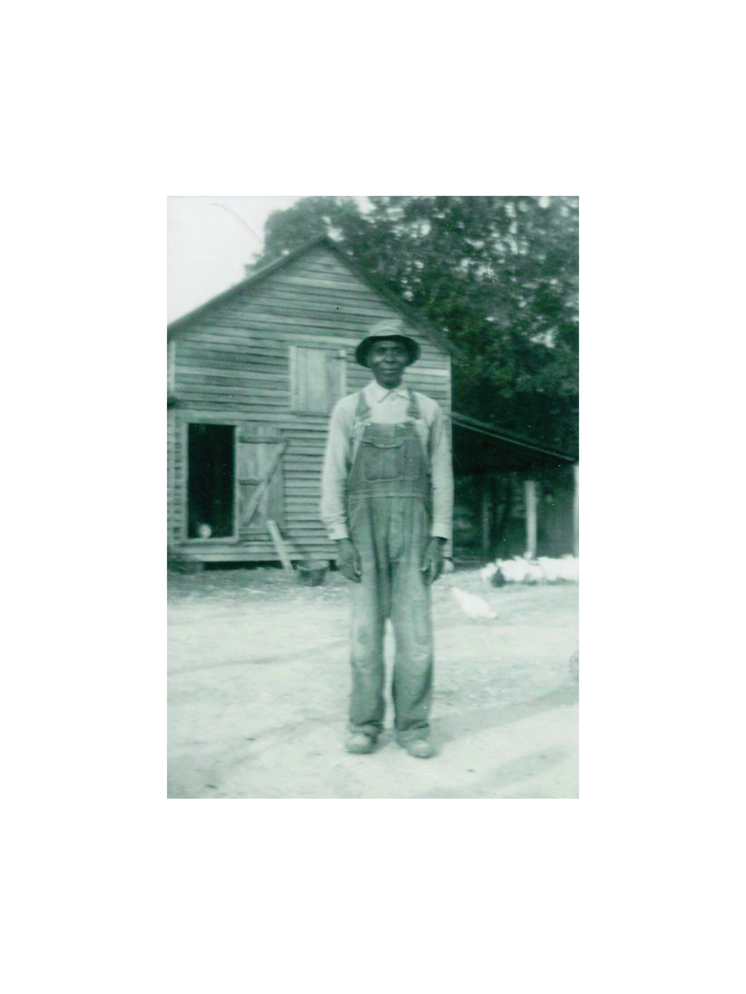 My Great Great Grandfather, in denim overalls, at his farm with his chickens.