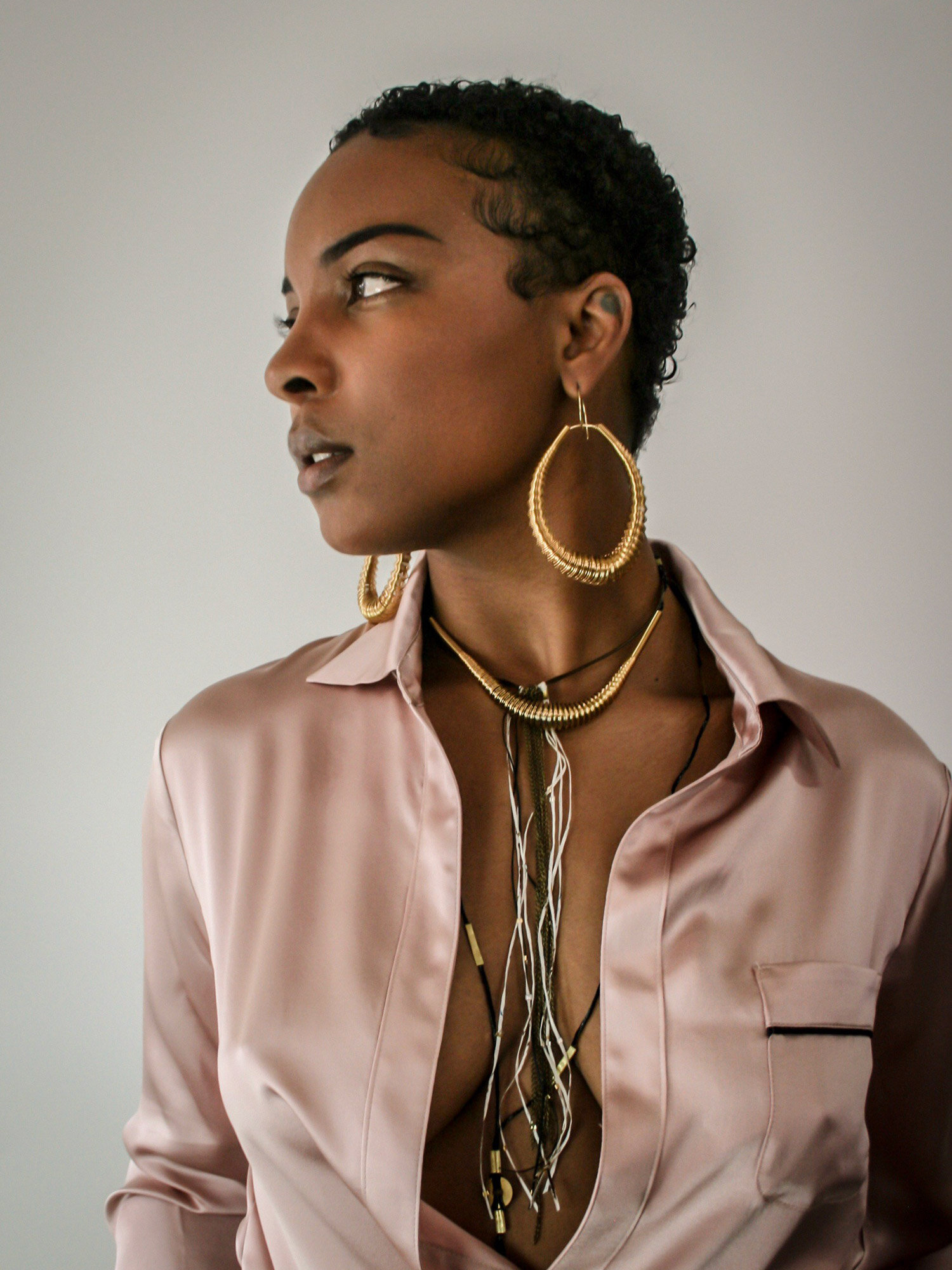 a statement pair of handcrafted millepiede earrings and a millepiede piccolo necklace pair with a medusa necklace and an anellide con occhio necklace create a layered and boho-chic look on this model wearing a Lotte99 shirt.