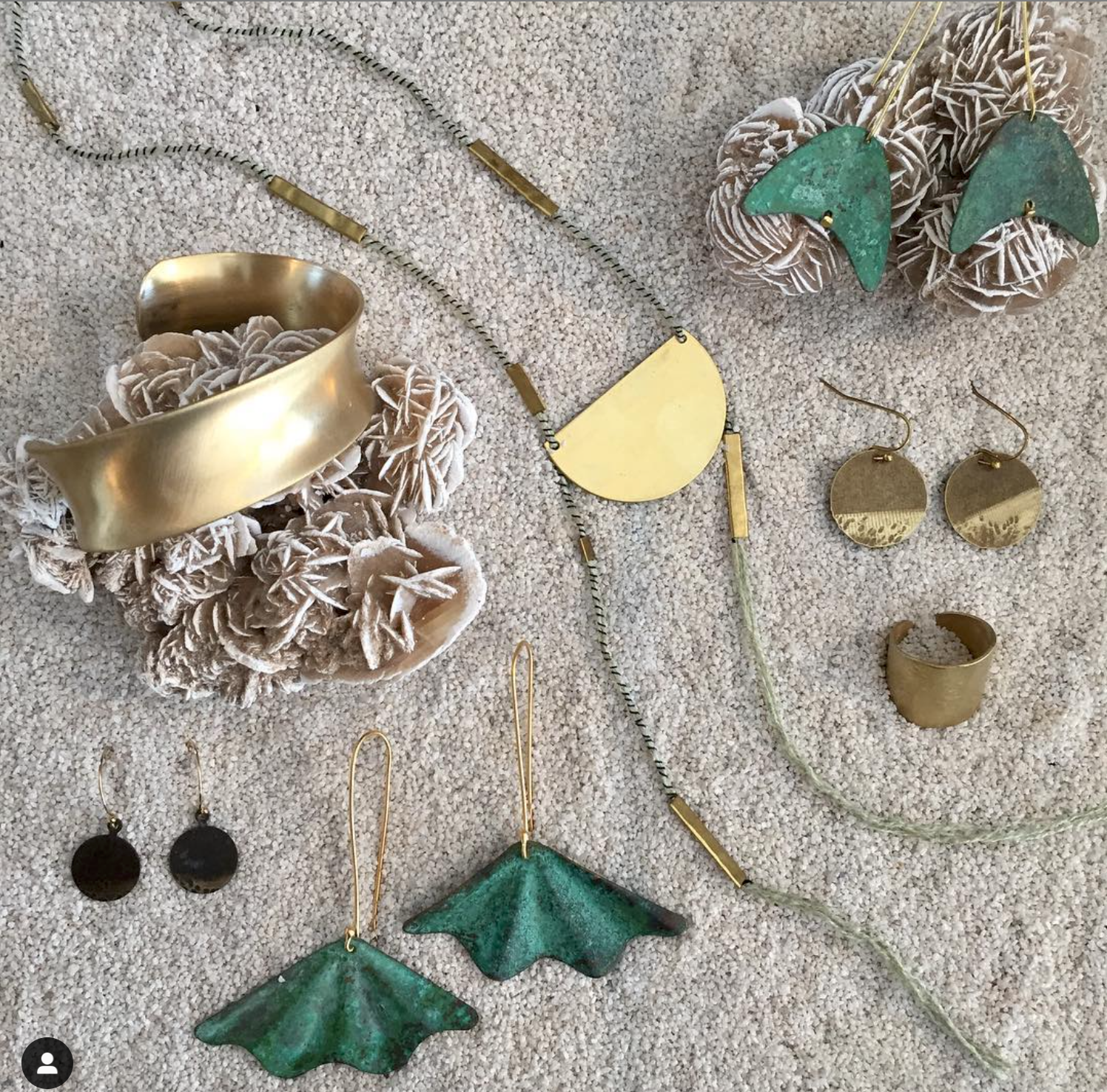 A selection of handmade Maddalena Bearzi metal and textile pieces displayed on sand and desert rose crystals for a beautiful and unique display-case. This jewelry is available at Dacha and in our online shop. Image: ©Dacha