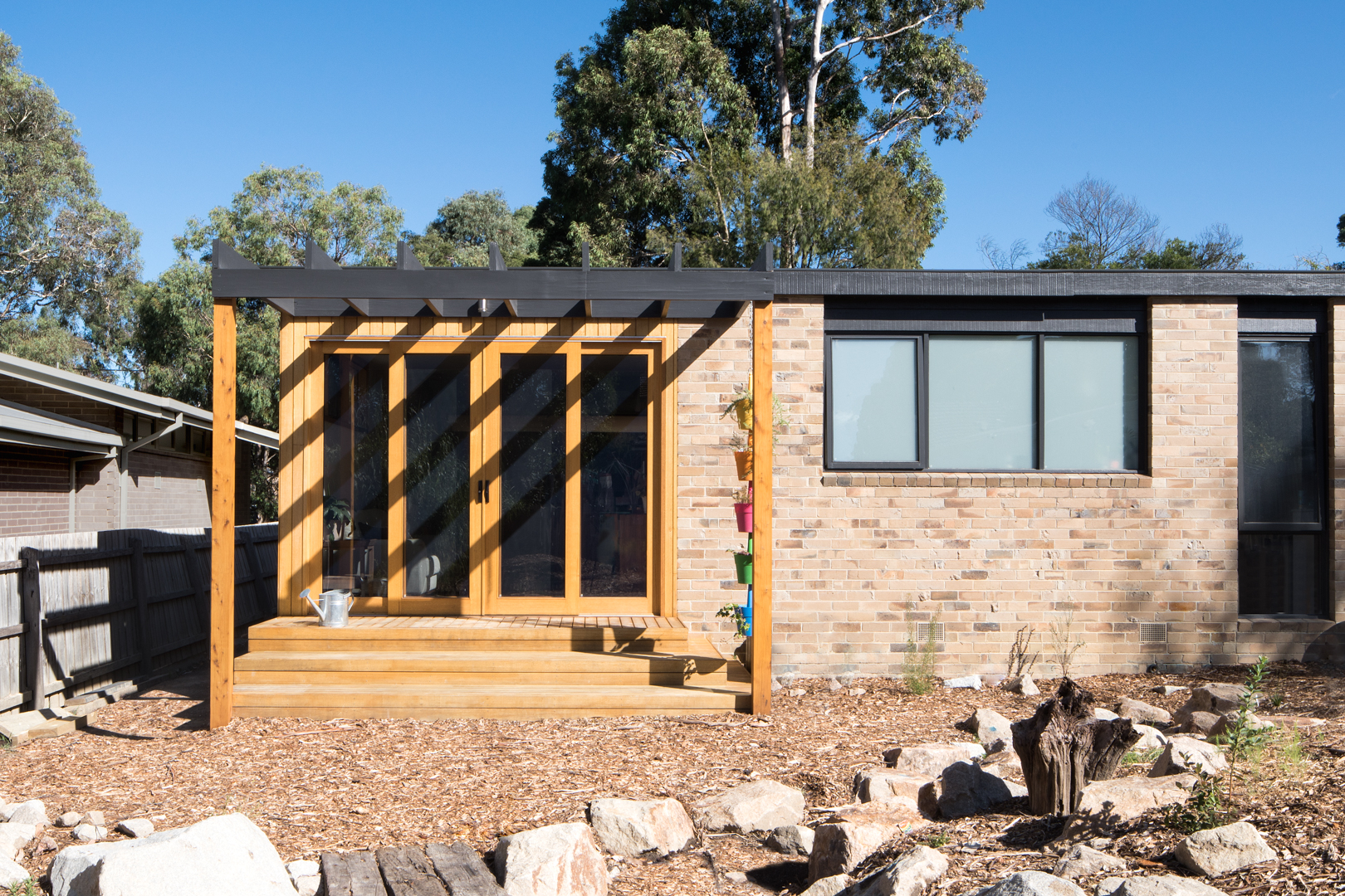 Rear extension with Vic Ash feature shiplap cladding, Vic Ash decking, Cypress feature posts, Australian Hardwood double glazed windows and doors.  Photography by Charlie Kinross