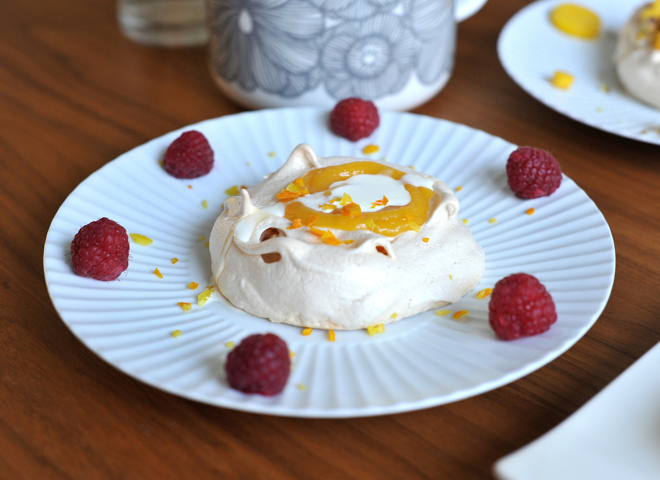 Meringue topped with lemon curd, zest of lemons and oranges served with raspberries and cream © Photography by Emmerline Smy