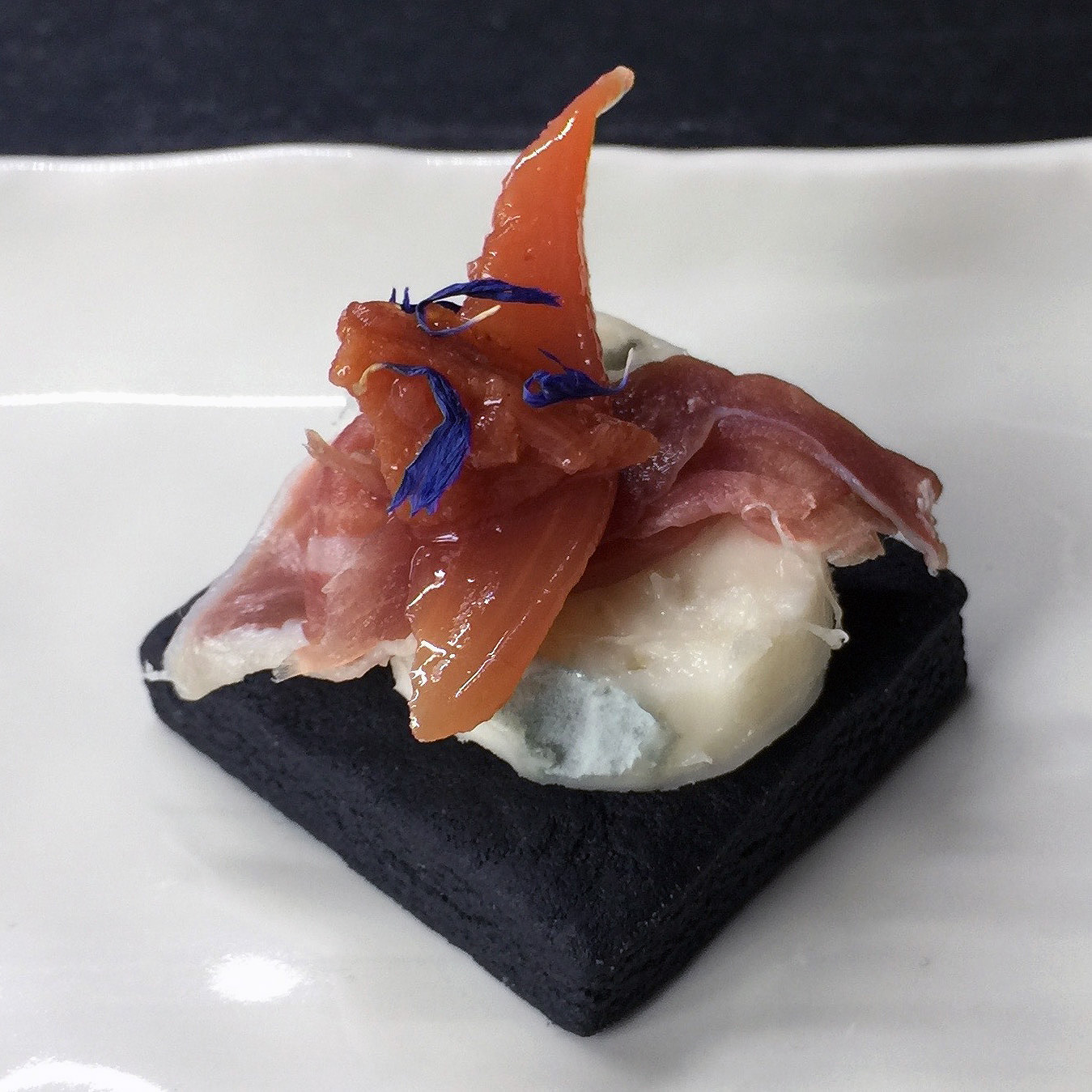 Charcoal biscuit with gorgonzola, prosciutto, quince chutney and dried cornflower garnish.