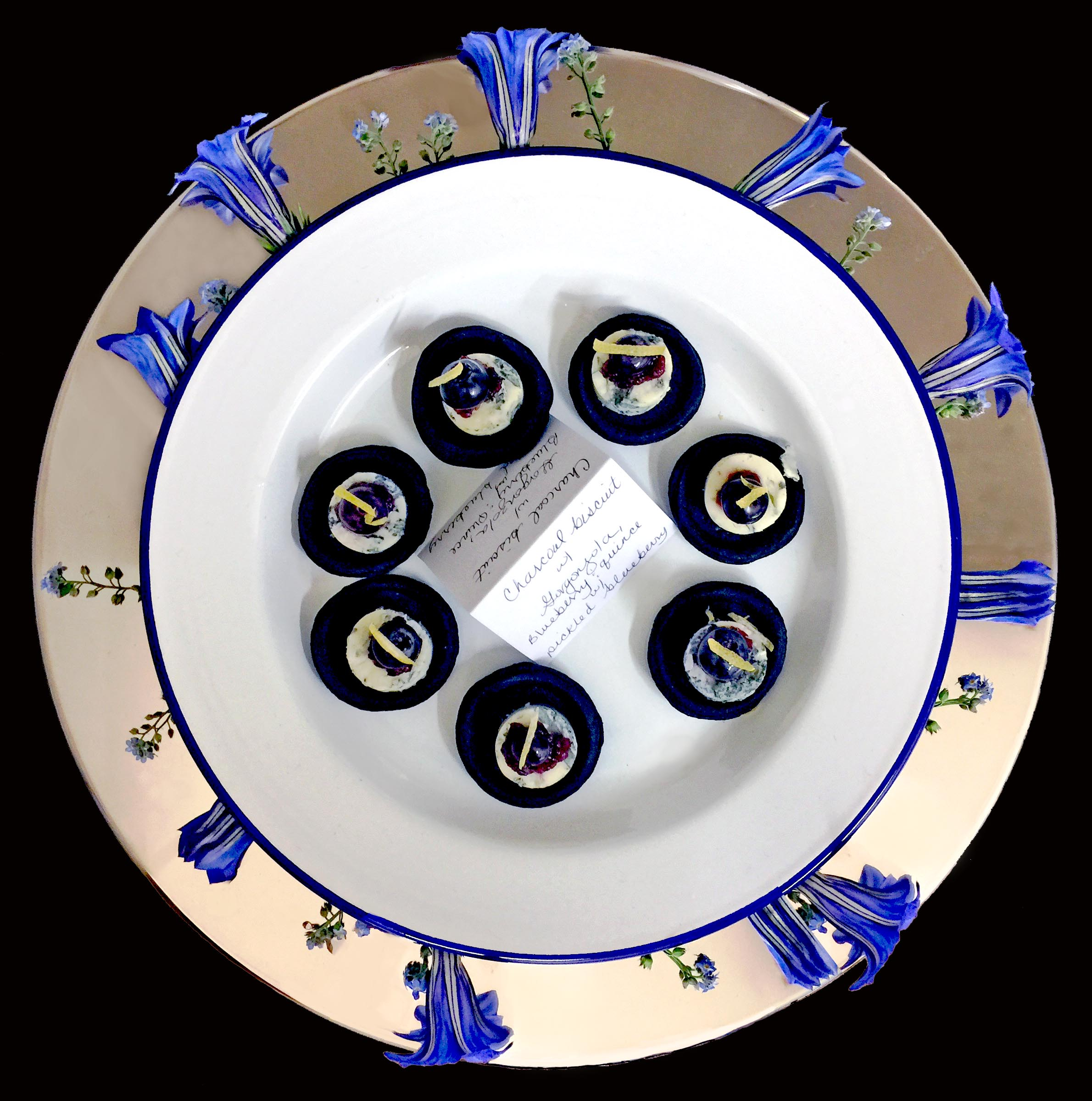 Tray of charcoal biscuit canapés served on an enamel plate within a sterling silver inset plate and decorated with fresh forget-me-not and gentiana flowers.