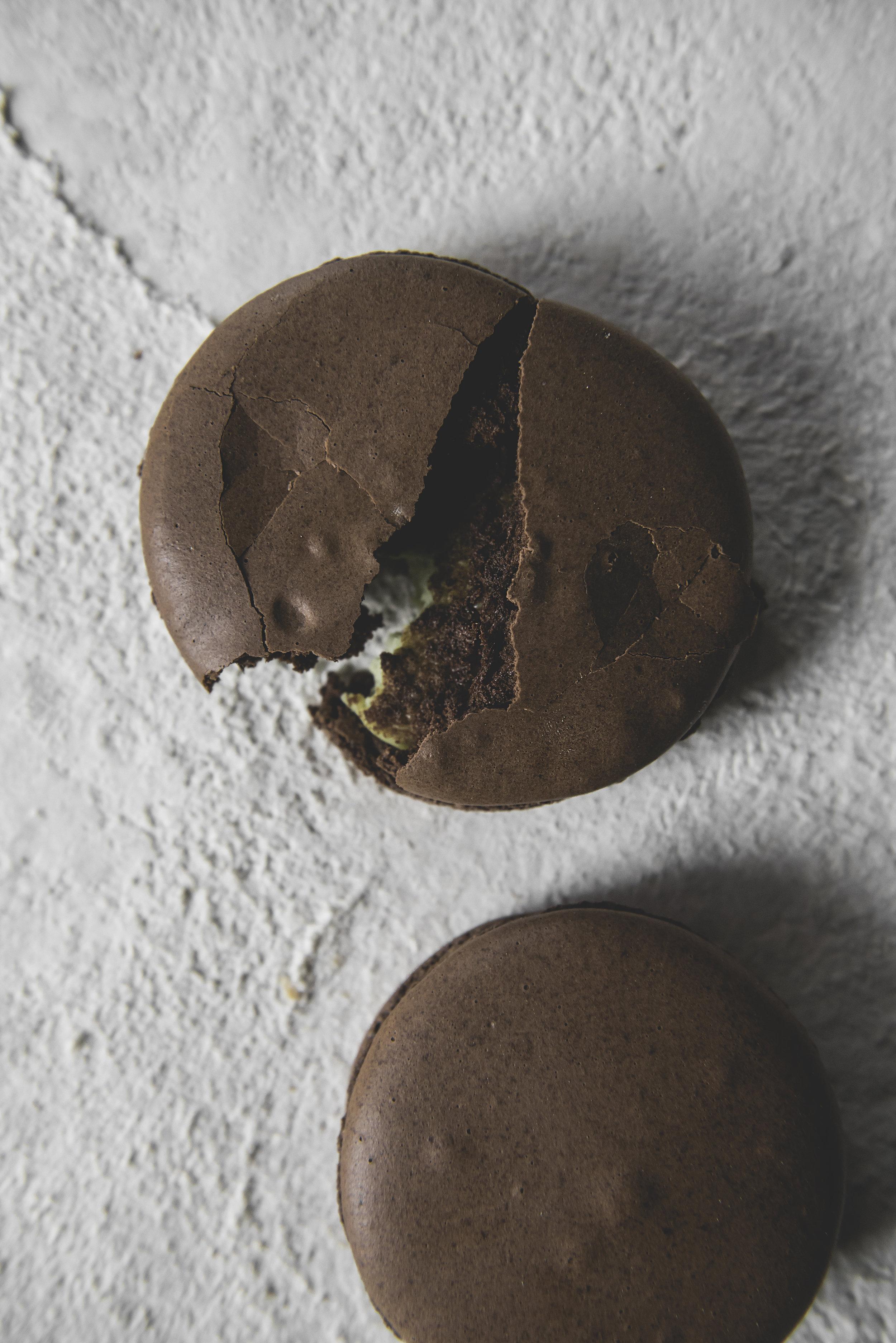 Chocolate Avocado Macaron - Chocolate macaron shell with a white chocolate avocado filling. Pair with a milky macchiato.