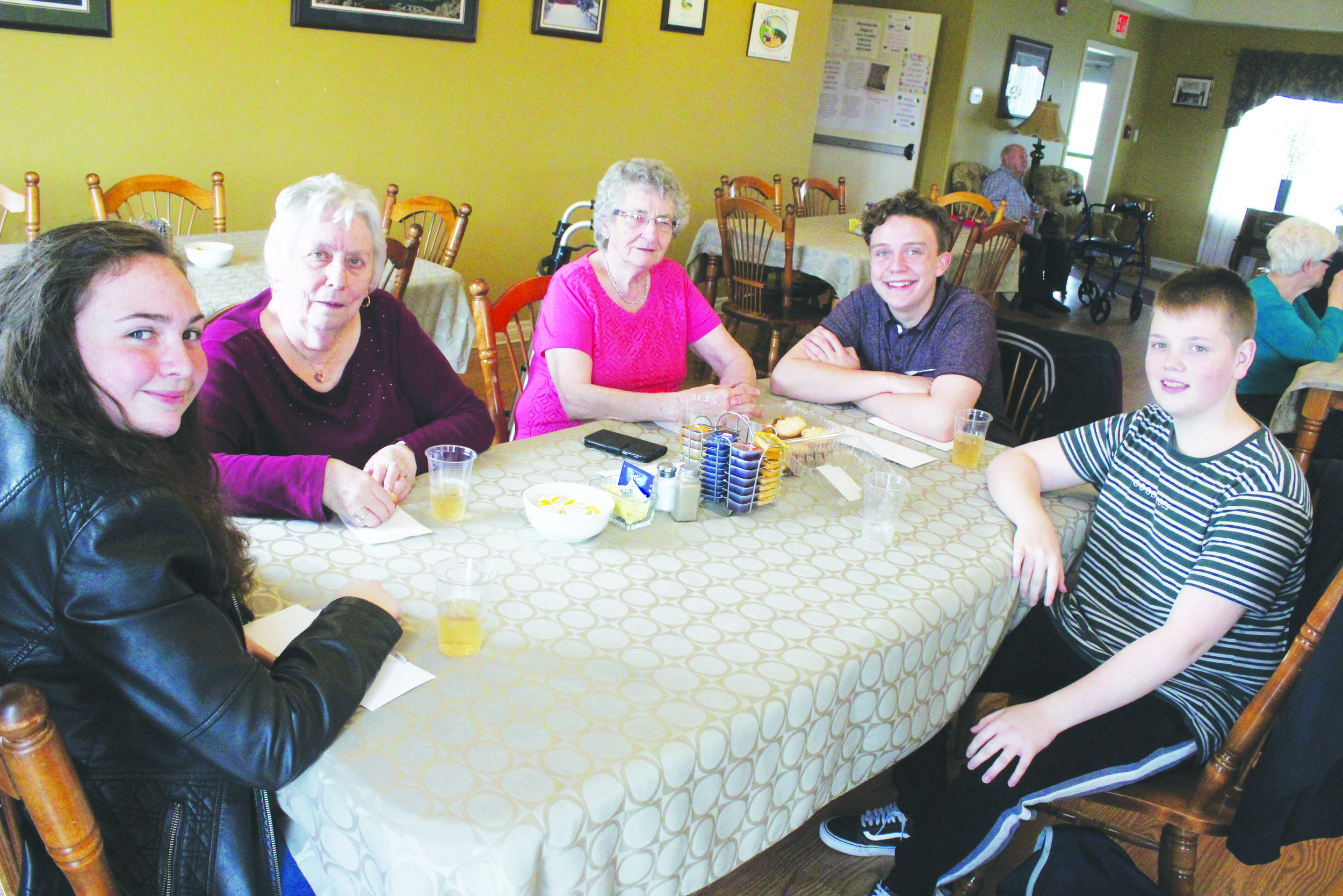 Members of the St. Kevin's social justice club and residents at Ruby Manor got to meet face-to-face after writing pen pal letters to one another over the last several months. Here ,from left to right, Holley Hennessey, Marguerite Hoyles, Violet Bixby, Isaac Shannahan, and Joey Williams.  Mark Squibb photo