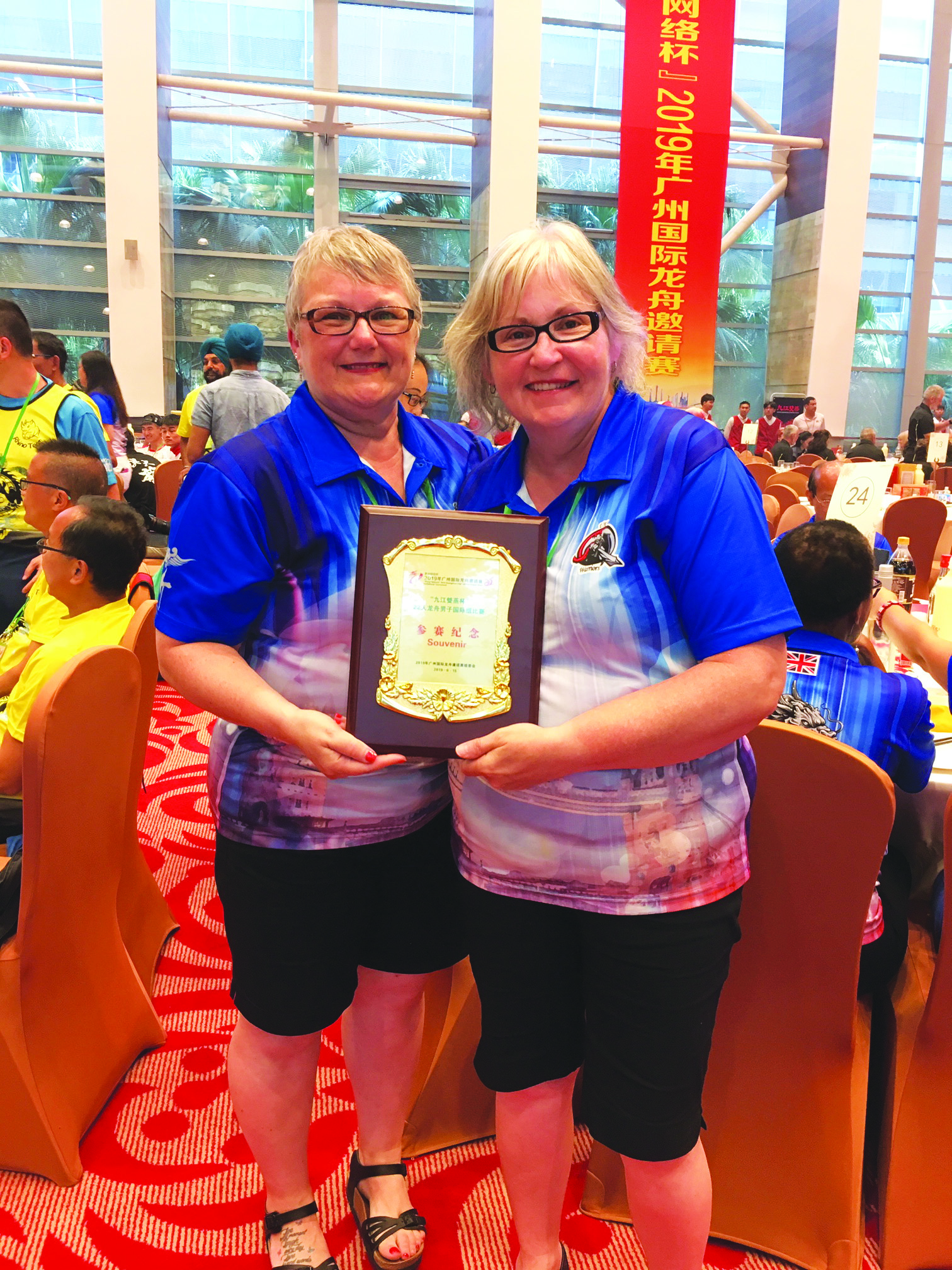 Kitty Whalen (left) and Kay Aylward with a souvenir plaque awarded to their Dragon Boat team in China.