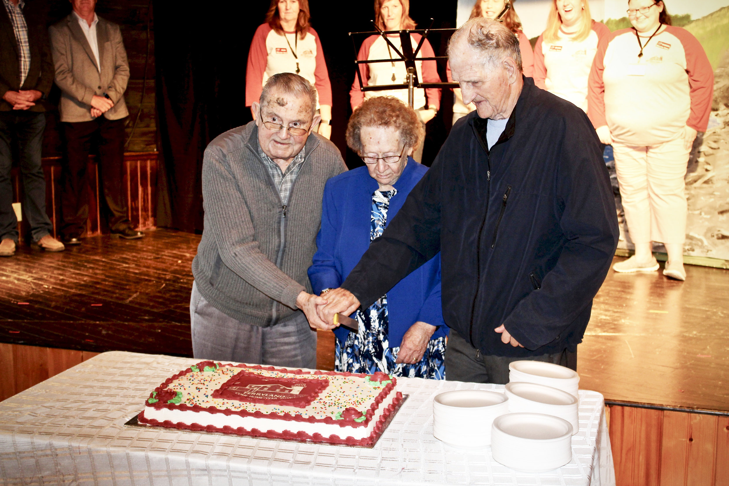 From left to right, Doug Windsor, Joan Costello and Phil Paul, Ferryland's three eldest residents, cut the Come Home year cake during the Opening Ceremonies. Nathan Ryan Photography